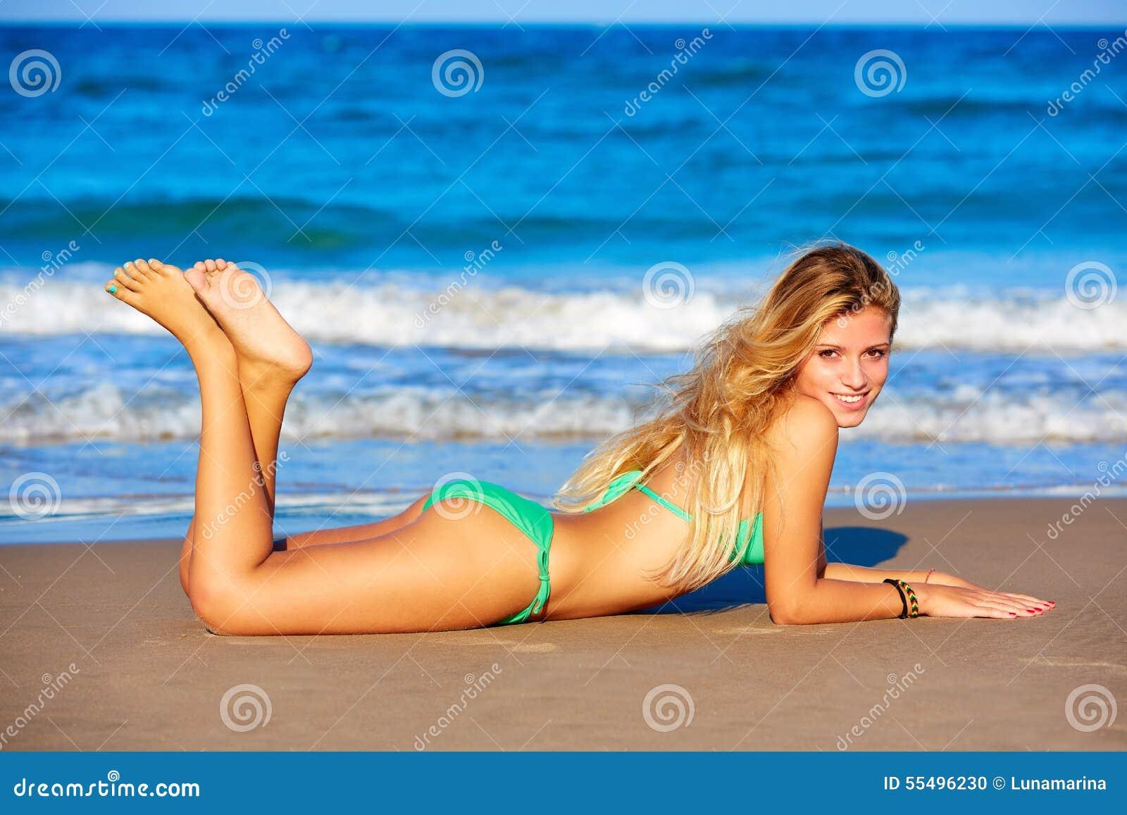 Ξανθές νεολαίες κοριτσιών μπικινιών που βρίσκονται στην άμμο παραλιών