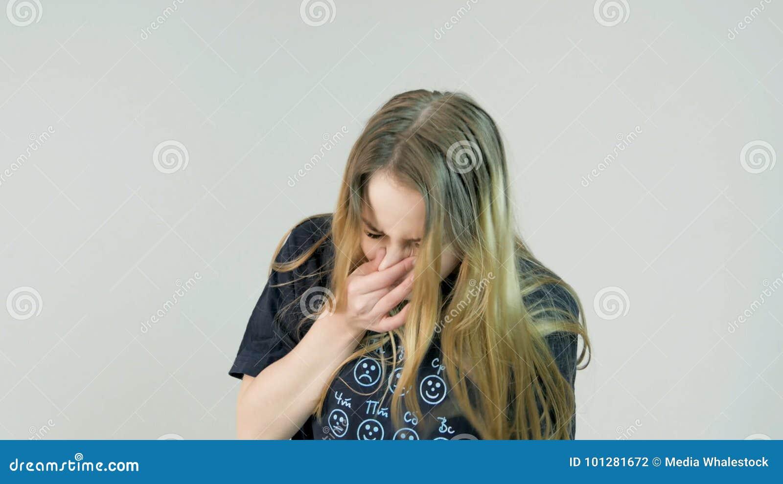 Ξανθή γυναίκα που φτερνίζεται στο άσπρο υπόβαθρο