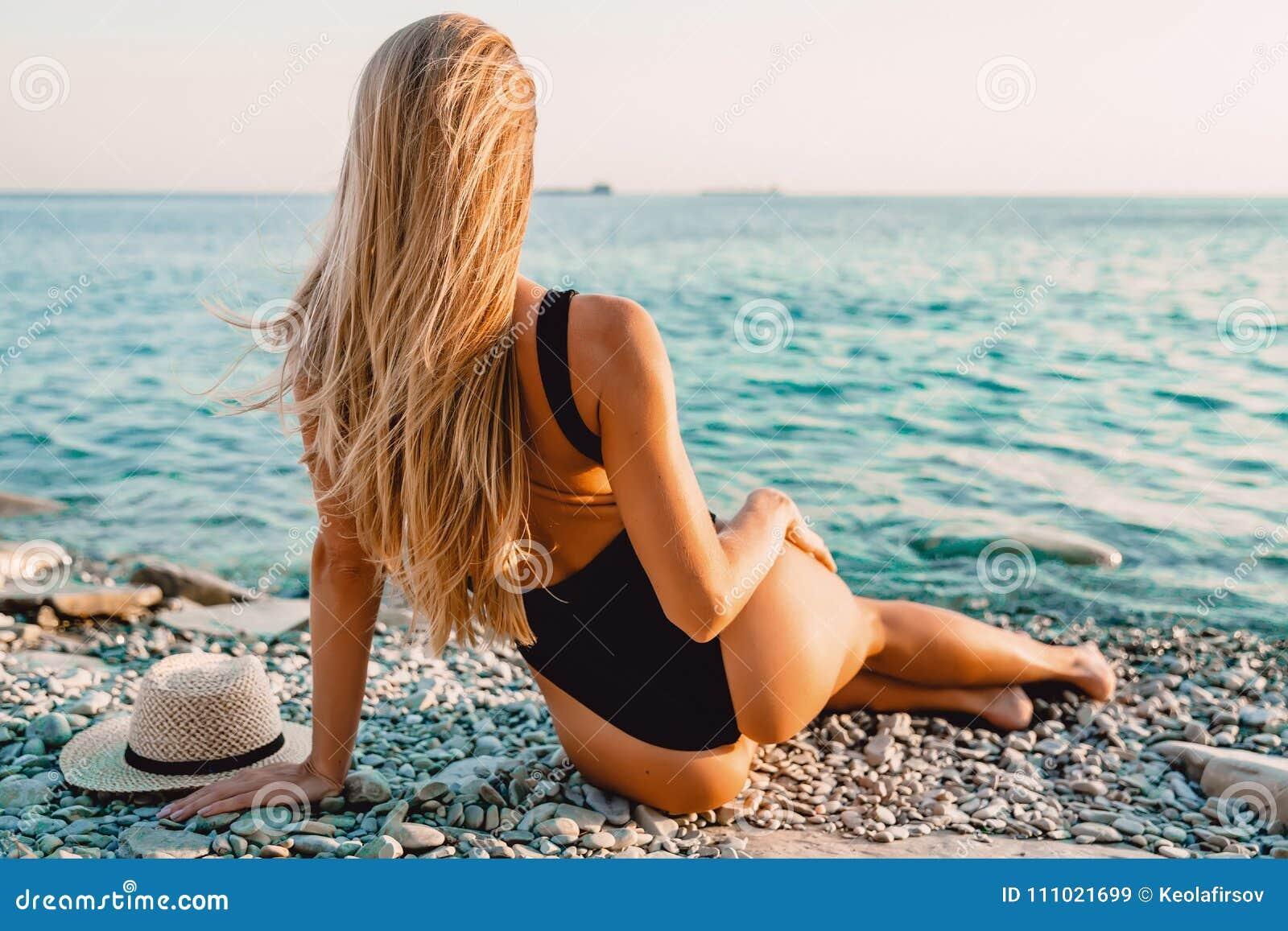 9999515bc06 Ξανθή γυναίκα στη μαύρη Swimwear χαλάρωση στη θάλασσα Στοκ Εικόνα ...