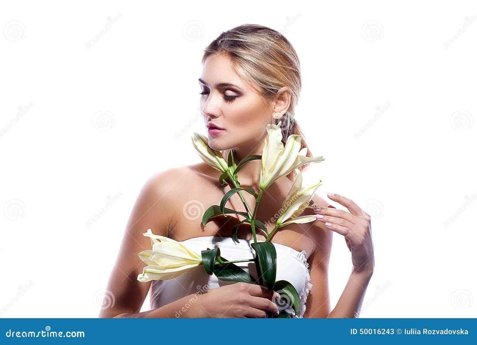 Ξανθή γυναίκα το φρέσκο καθαρό δέρμα και το άσπρο λουλούδι κρίνων που απομονώνονται με