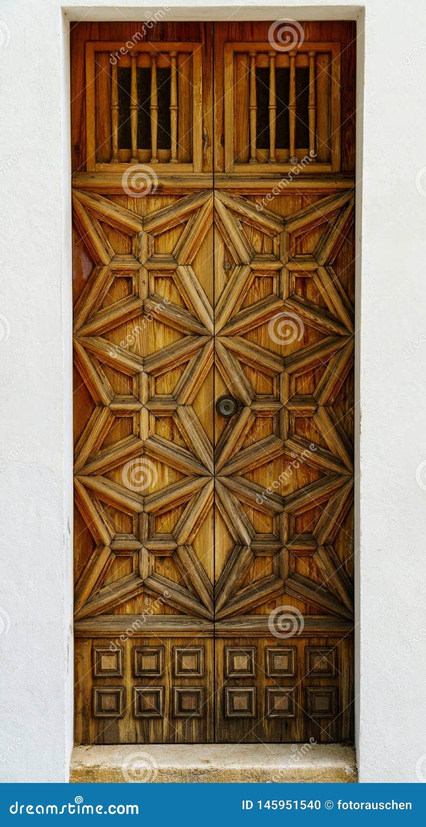 Ξεπερασμένη ξύλινη μπροστινή πόρτα με το περίκομψο ντεκόρ