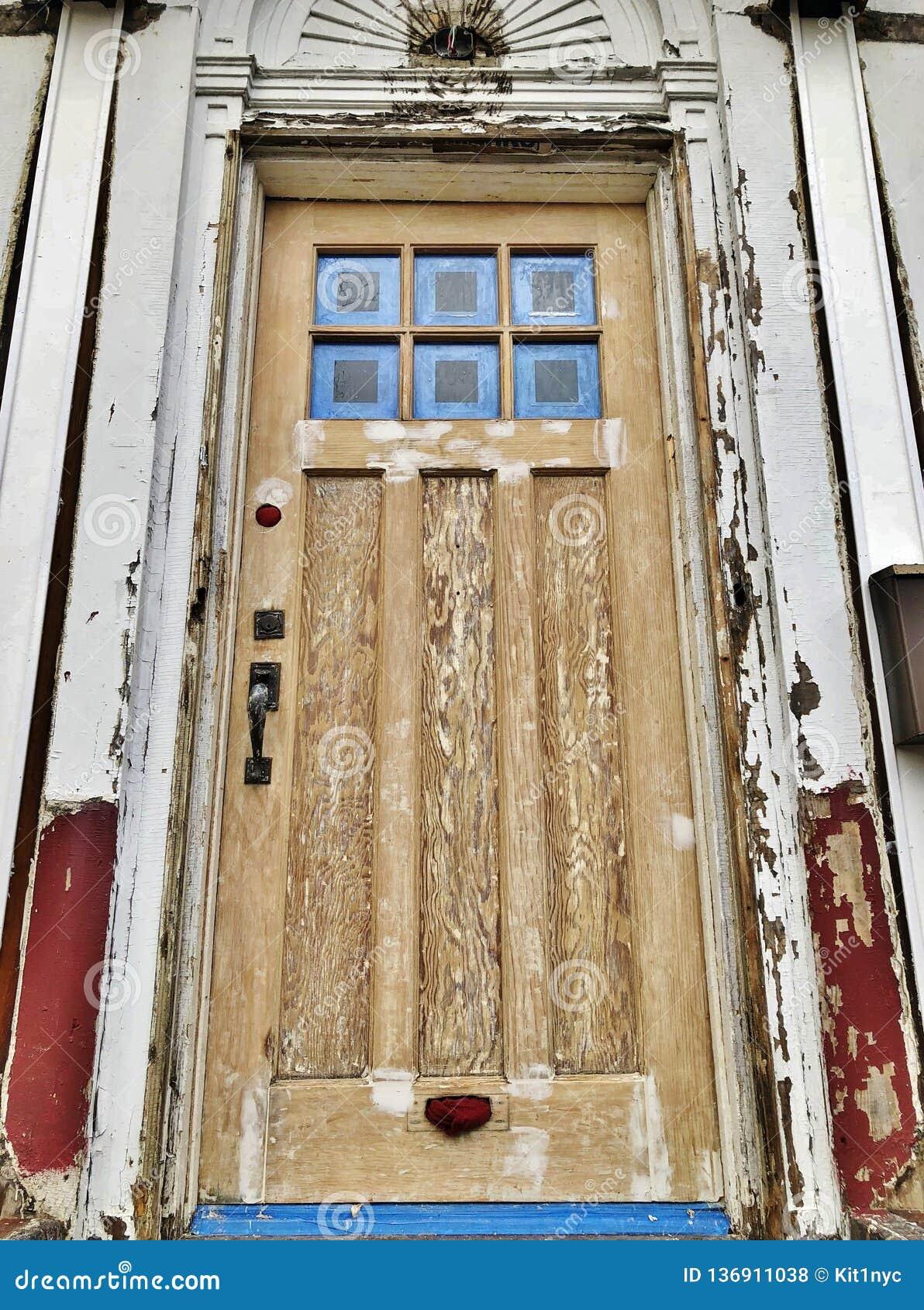 Ξεπερασμένη ραγισμένη μπροστινή πόρτα του παλαιού σπιτιού κάτω από την κατασκευή που χτίζει και που επισκευάζει το νέο σπίτι