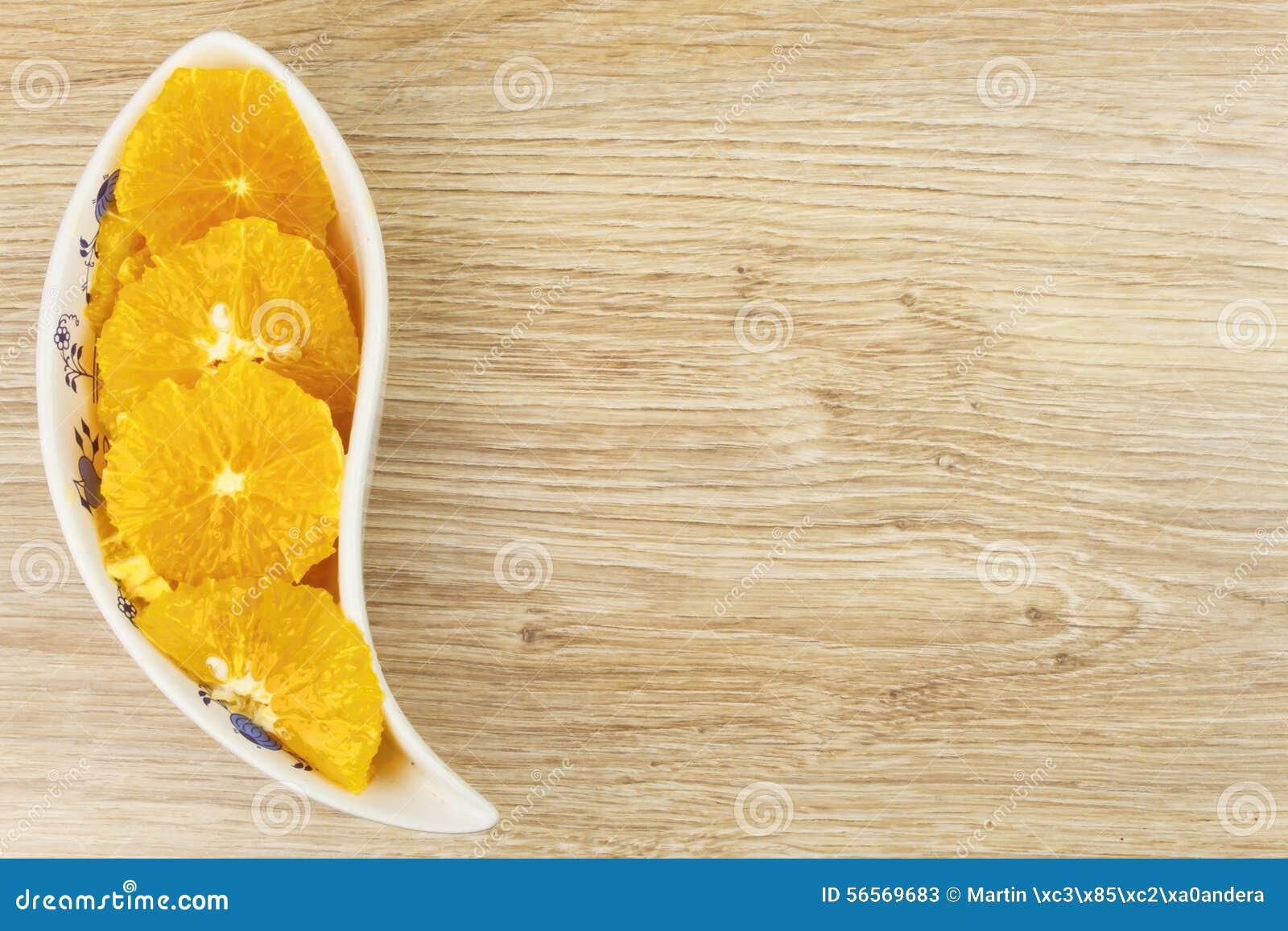Download Ξεφλουδισμένο και τεμαχισμένο πορτοκάλι σε ένα κύπελλο πορσελάνης Στοκ Εικόνα - εικόνα από fruity, γεωργίας: 56569683