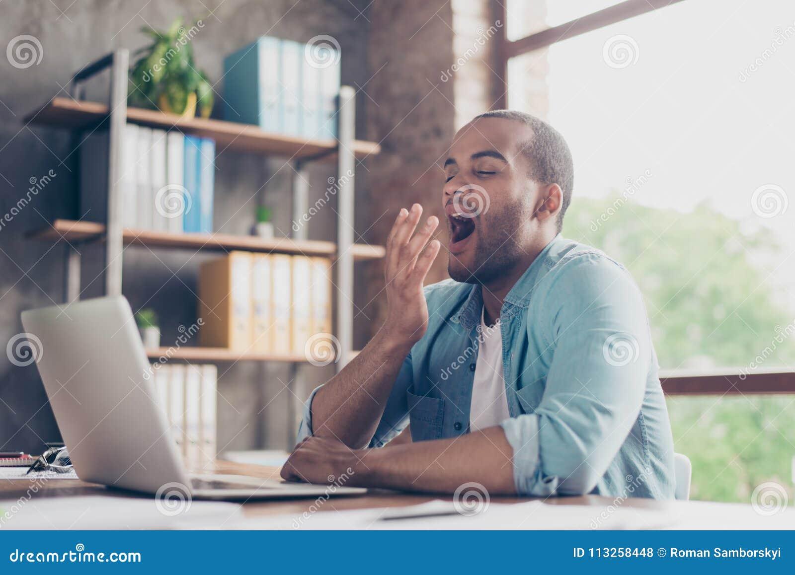 Ξημερώματα στο γραφείο Νυσταλέος που κουράζεται freelancer χασμουριέται στο χώρο εργασίας του μπροστά από την οθόνη lap-top ` s σ