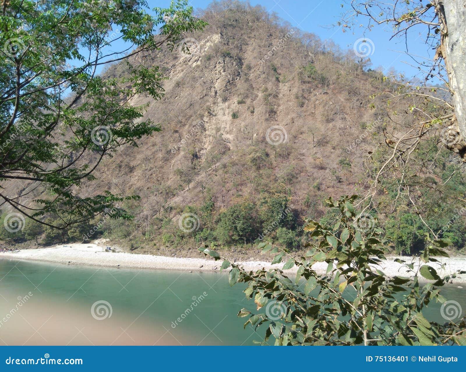 Ξηρό βουνό με τη λίμνη και δέντρα στο επιδόρπιο