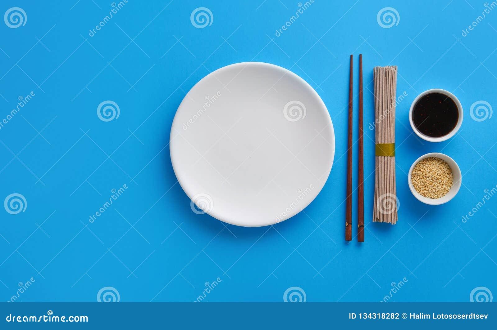 Ξηρό soba νουντλς με τη σάλτσα σόγιας, το σουσάμι και chopsticks σε ένα μπλε υπόβαθρο Επίπεδος βάλτε με τη τοπ άποψη