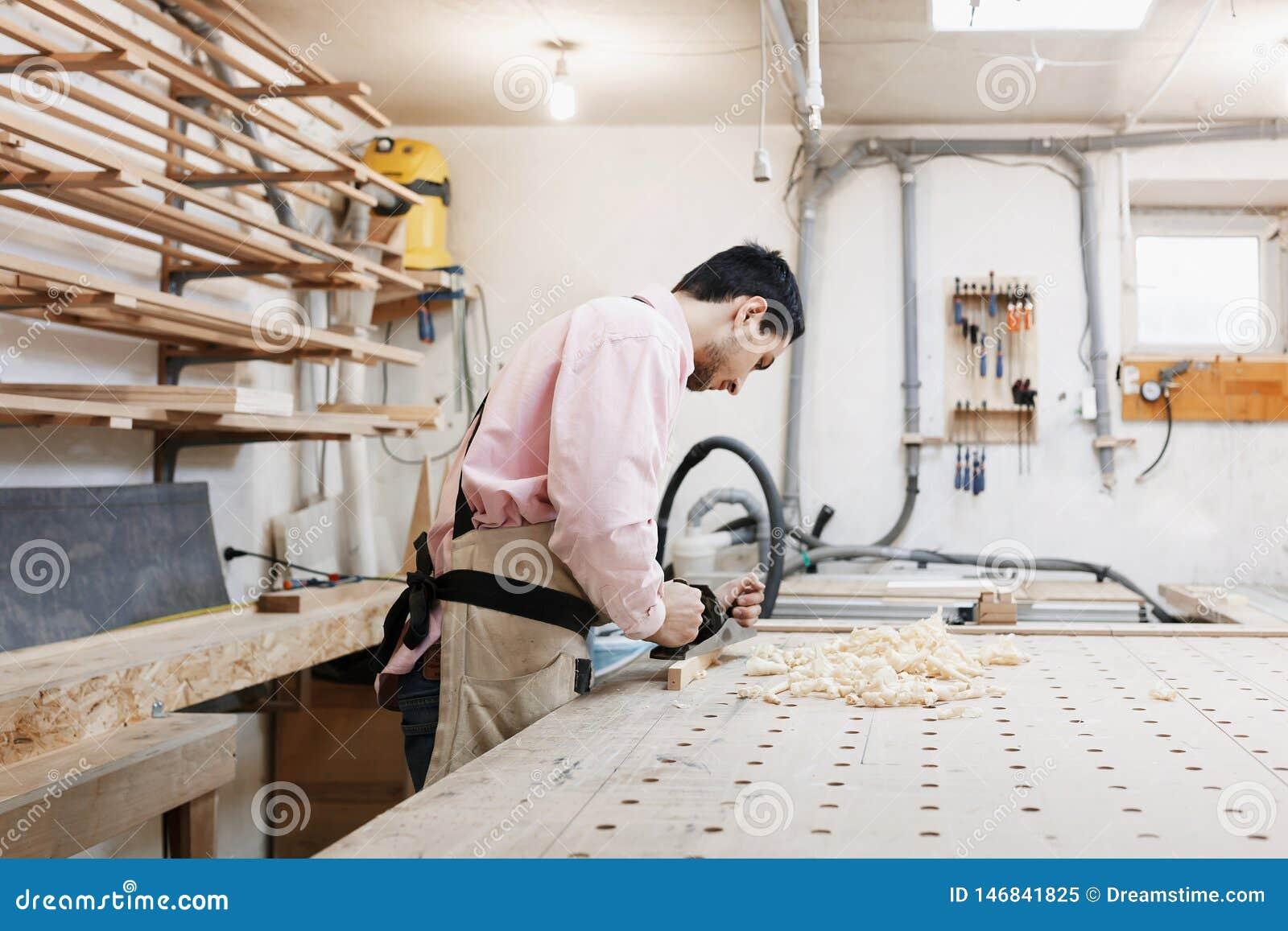 Ξυλουργός που εργάζεται με το αεροπλάνο και την ξύλινη σανίδα στο εργαστήριο