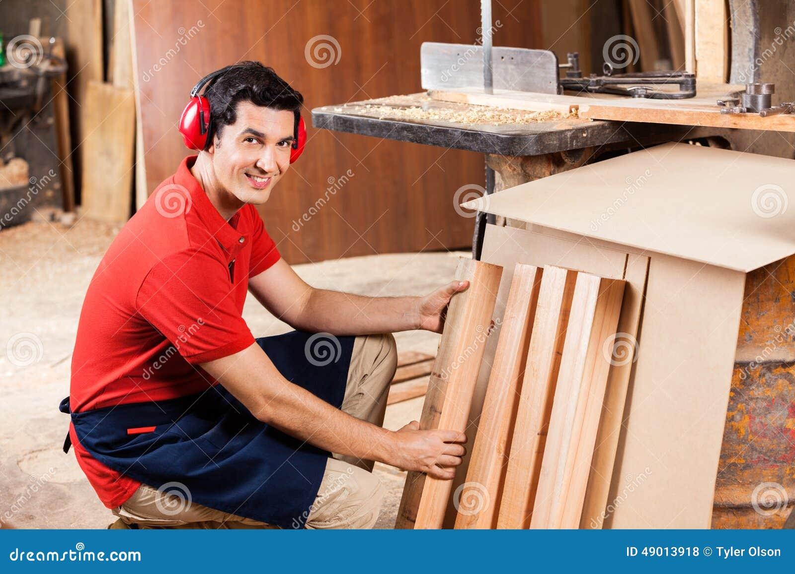 Ξυλουργός που τακτοποιεί τις ξύλινες σανίδες στο εργαστήριο