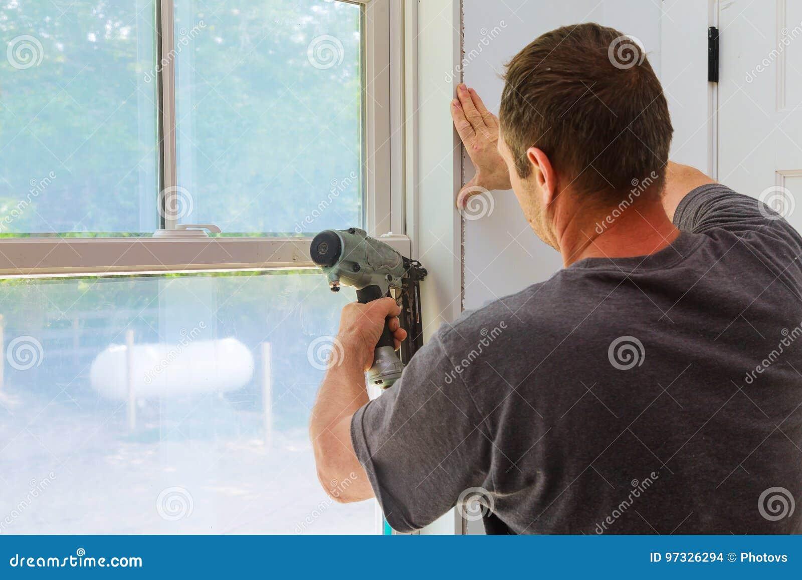 Ξυλουργός που χρησιμοποιεί το πυροβόλο όπλο καρφιών στις σχηματοποιήσεις στα παράθυρα, που πλαισιώνουν την περιποίηση,