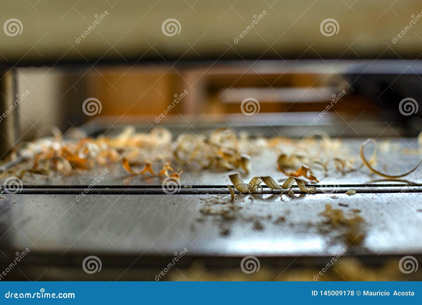 Ξύλινα τσιπ σε μια μηχανή πλανίσματος ξυλουργών