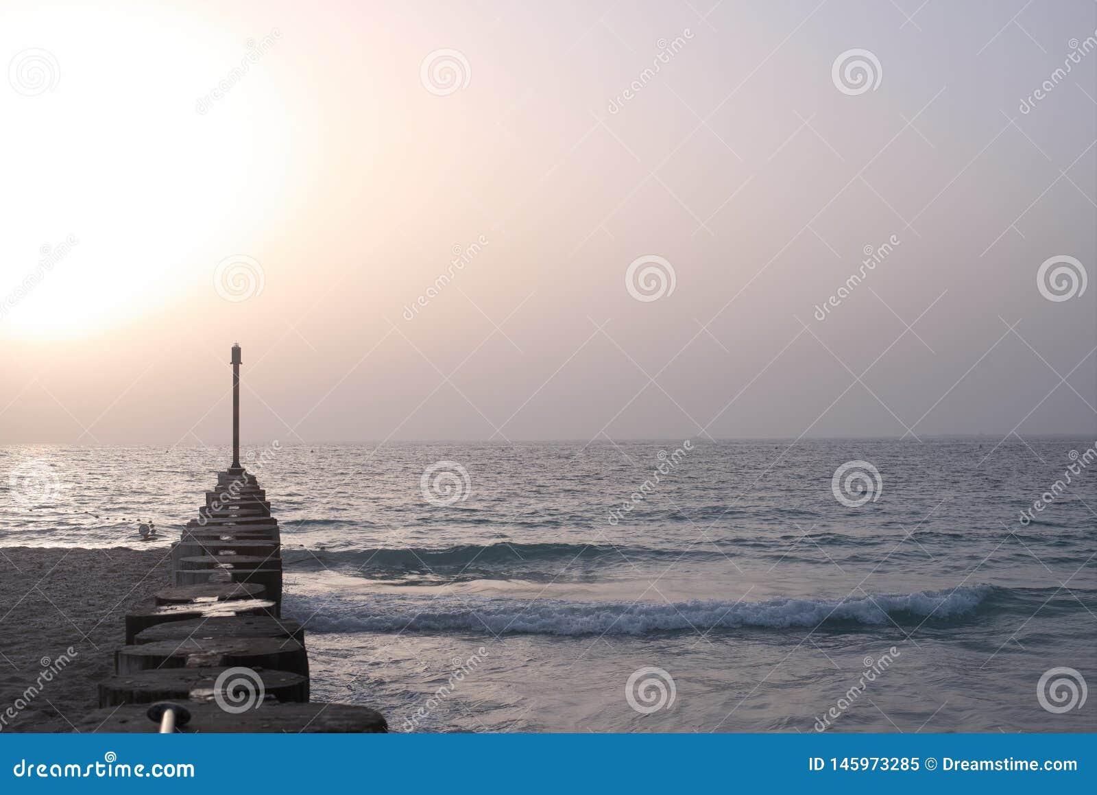 Ξύλινη αποβάθρα με τους στυλοβάτες στην παραλία θερινού λυκόφατος