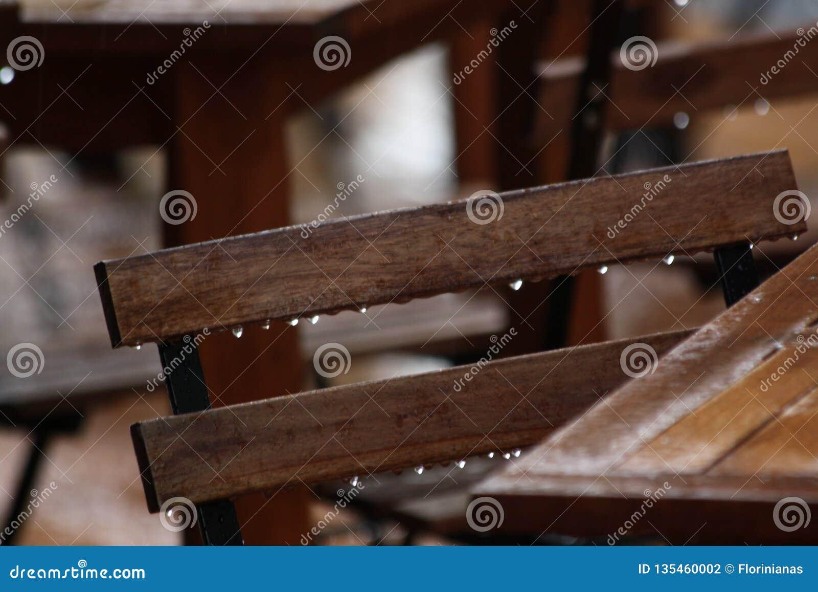 Ξύλινοι καρέκλα και πίνακας από έναν καφέ στη βροχή Υγρά αστικά έπιπλα