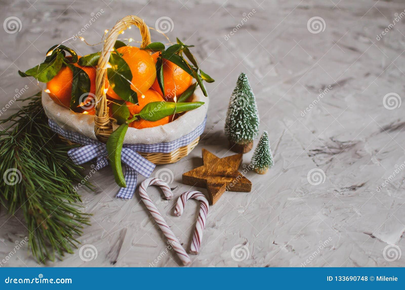 Ξύλινο μανταρίνι καλαθιών με τα φύλλα και φω τα, Tangerine πορτοκάλι στα γκρίζα επιτραπέζιου υποβάθρου ντεκόρ έτους Χριστουγέννων