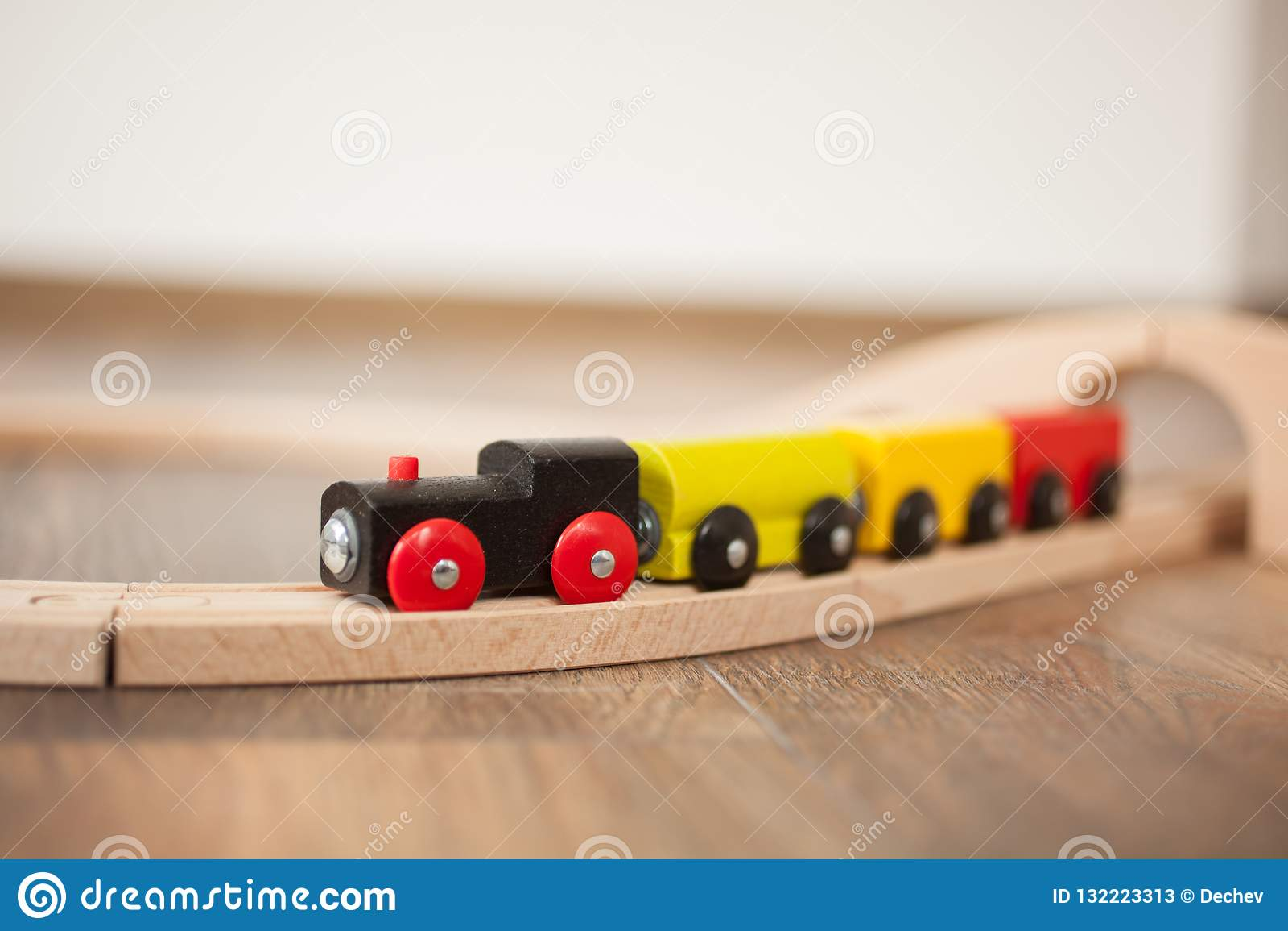Ξύλινο τραίνο παιχνιδιών στο σιδηρόδρομο με την ξύλινη γέφυρα Καθαρίστε το τοποθετημένο σε στρώματα πάτωμα