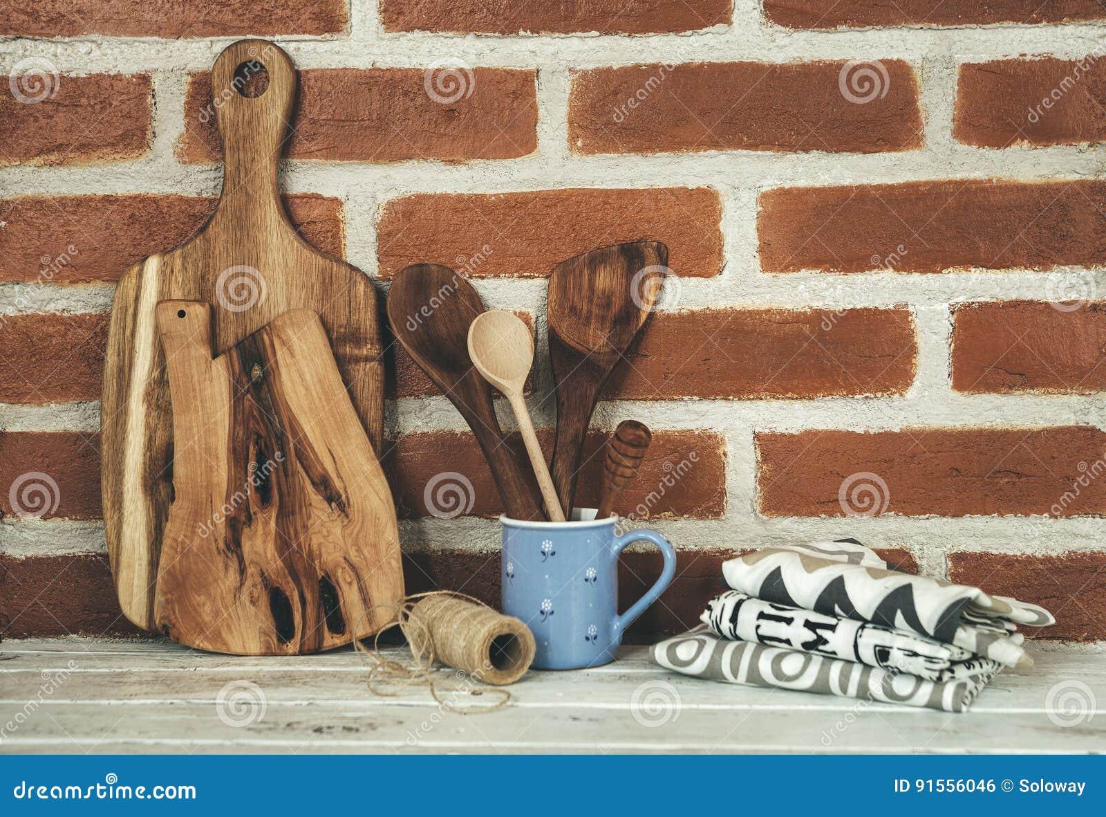 Ξύλινα στηρίγματα κουζινών στο υπόβαθρο τουβλότοιχος