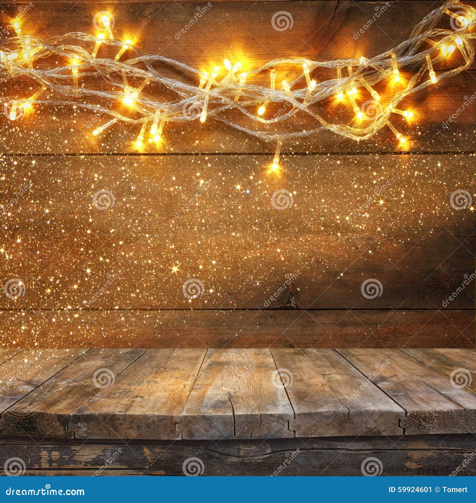 Ξύλινος πίνακας πινάκων μπροστά από τα θερμά χρυσά φω τα γιρλαντών Χριστουγέννων στο ξύλινο αγροτικό υπόβαθρο Φιλτραρισμένη εικόν
