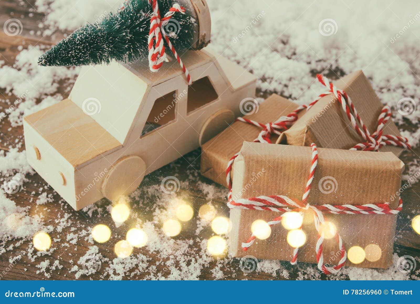 Ξύλινο αυτοκίνητο που φέρνει ένα δέντρο πεύκων δίπλα στα δώρα Χριστουγέννων