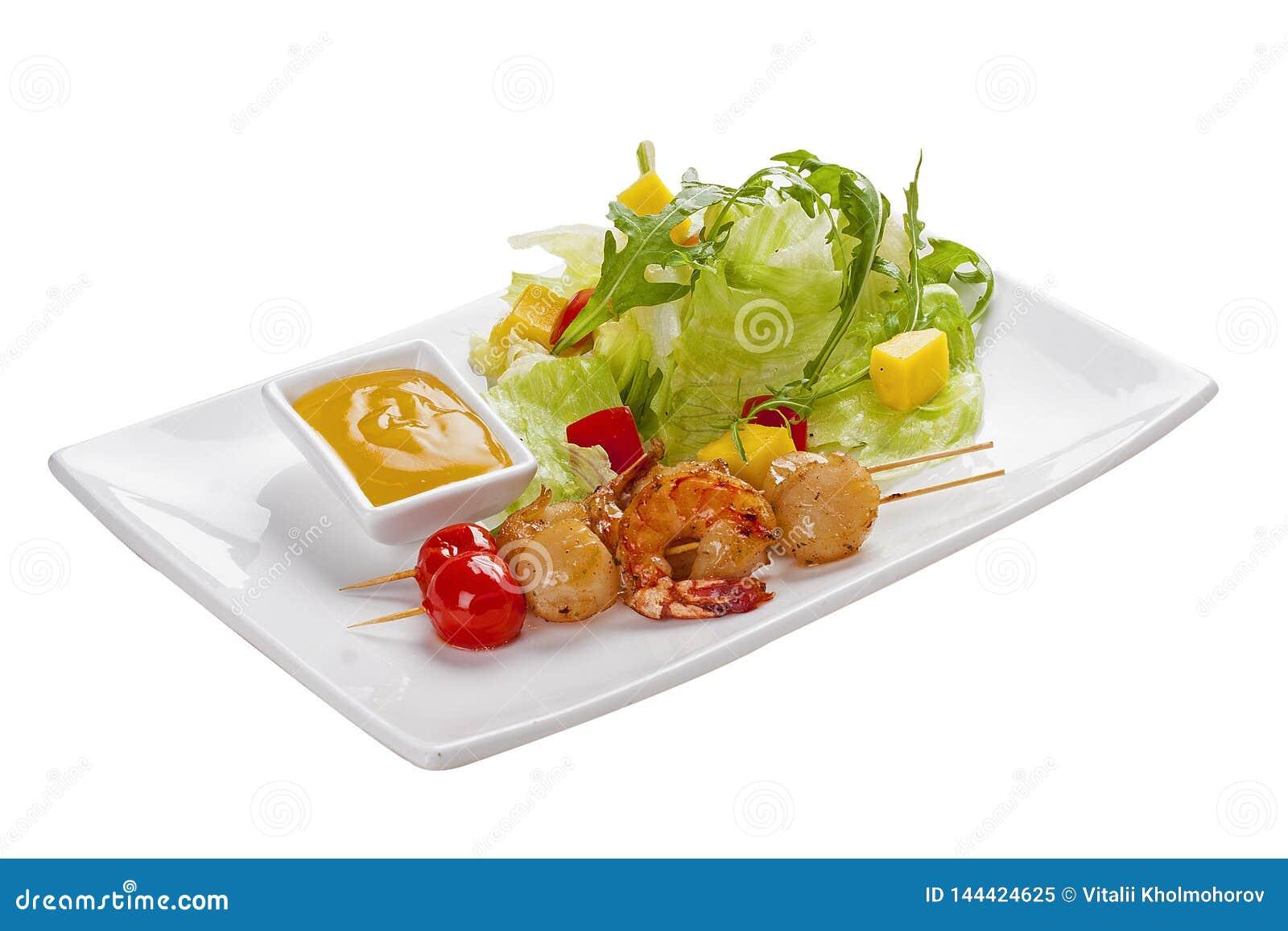 Οβελίδια των οστράκων και των γαρίδων Σε ένα άσπρο πιάτο