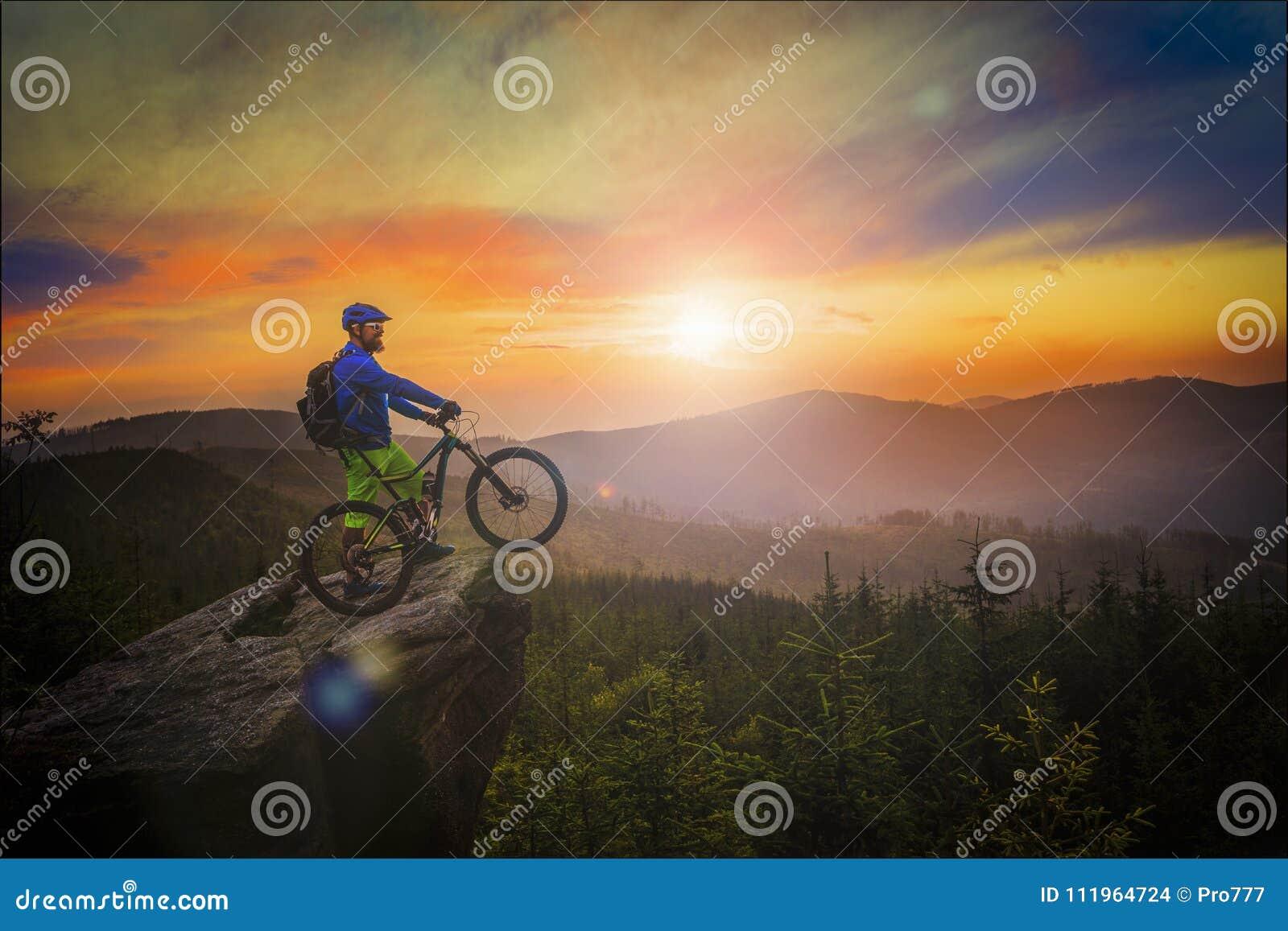 Οδήγηση ποδηλατών βουνών στο ηλιοβασίλεμα στο ποδήλατο στα θερινά βουνά εκ των προτέρων