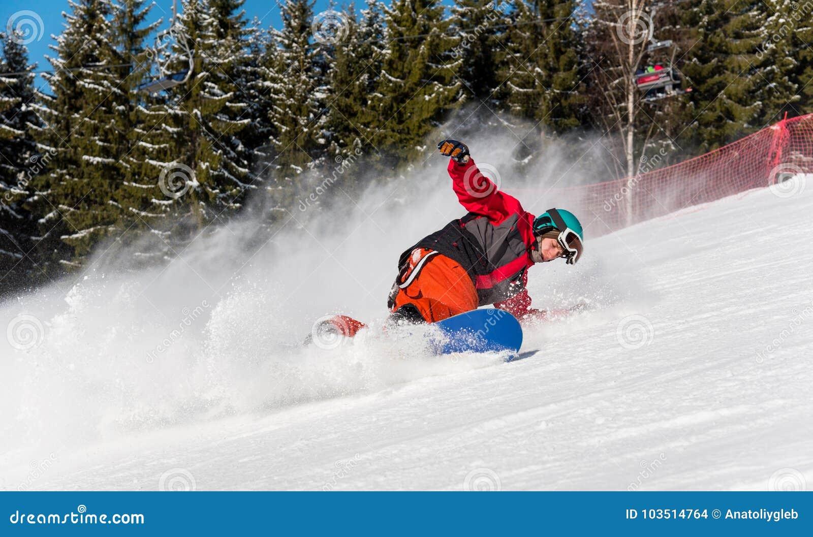 Οδήγηση Snowboarder στα βουνά σε μια ηλιόλουστη χειμερινή ημέρα
