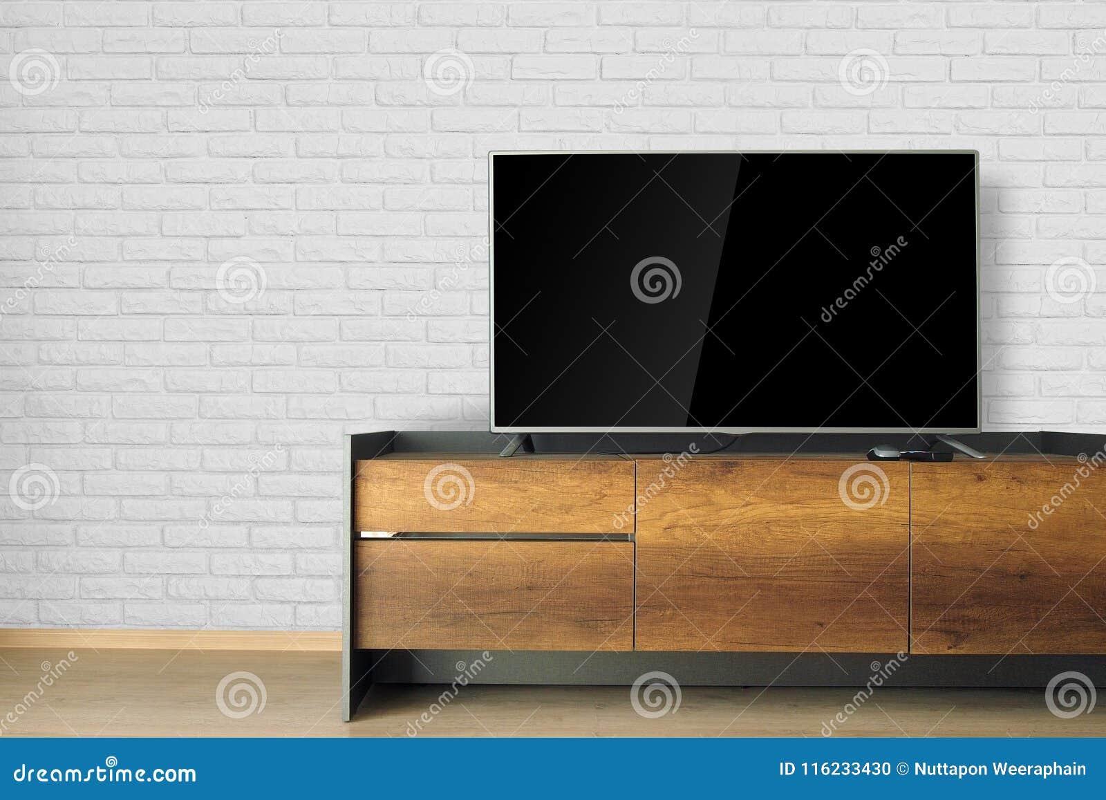 Οδηγημένη TV στη στάση TV στο κενό δωμάτιο με τον άσπρο τουβλότοιχο διακοσμήστε