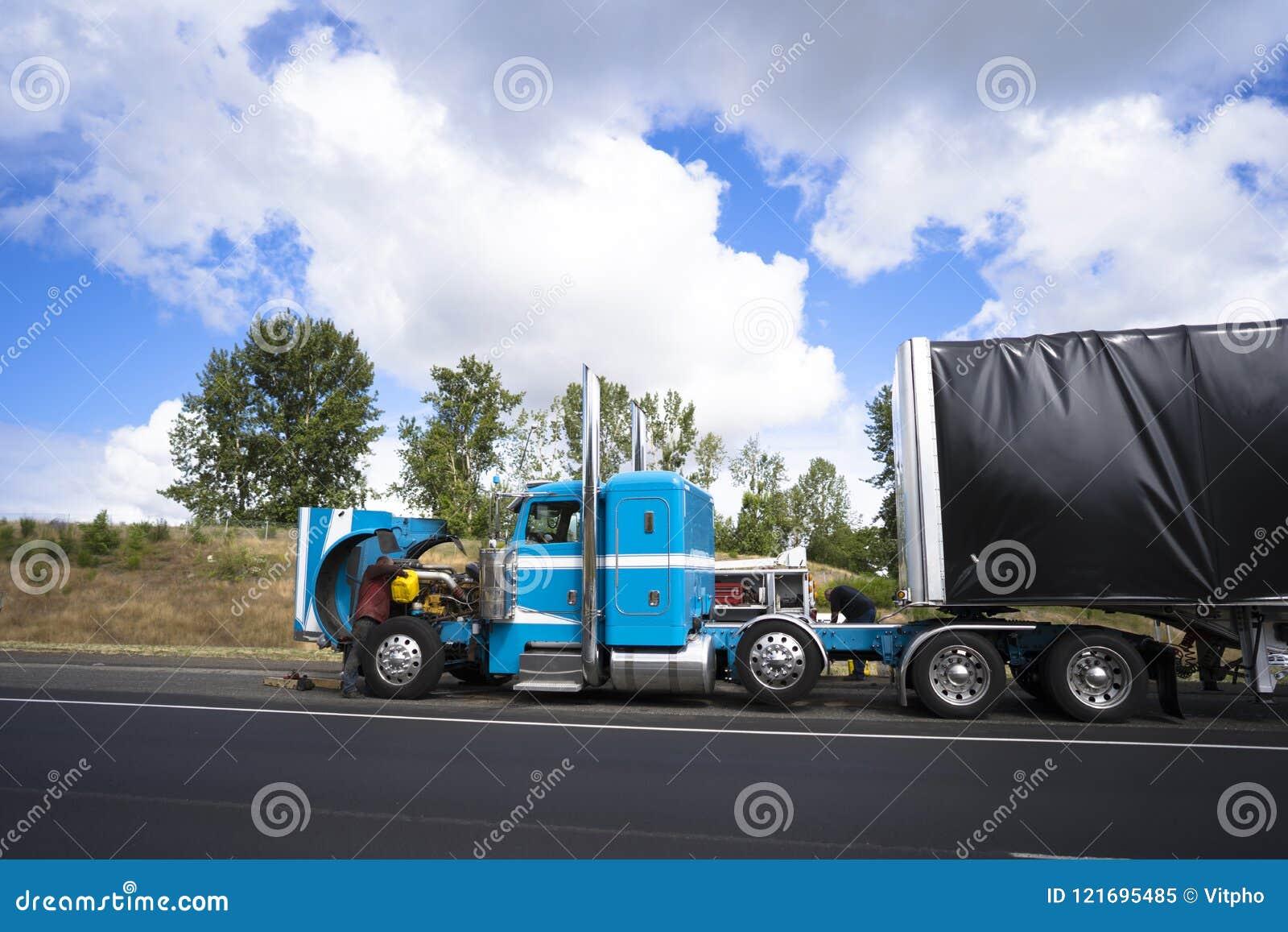 Οδηγοί φορτηγού που επισκευάζουν το μεγάλο ημι φορτηγό εγκαταστάσεων γεώτρησης με το ανοικτό δικαίωμα κουκουλών