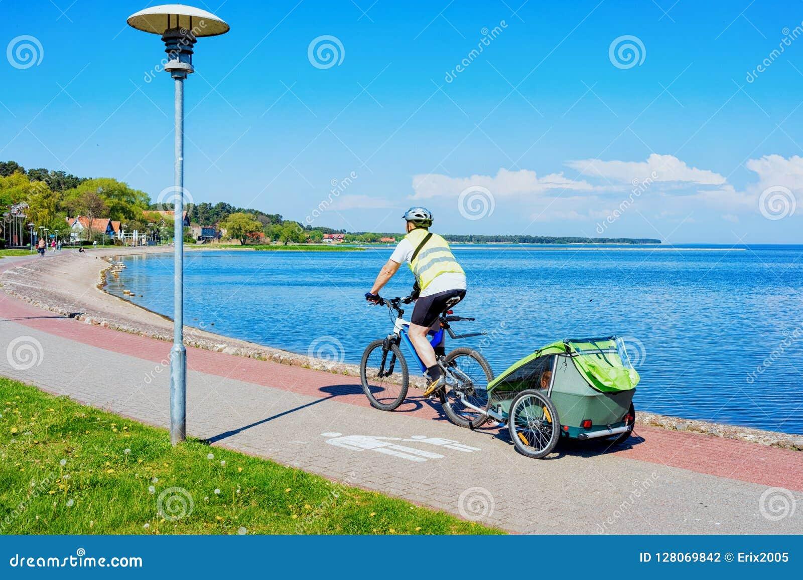 Οδηγώντας οβελός Curonian θερέτρου της Nida ποδηλάτων ατόμων και η θάλασσα της Βαλτικής