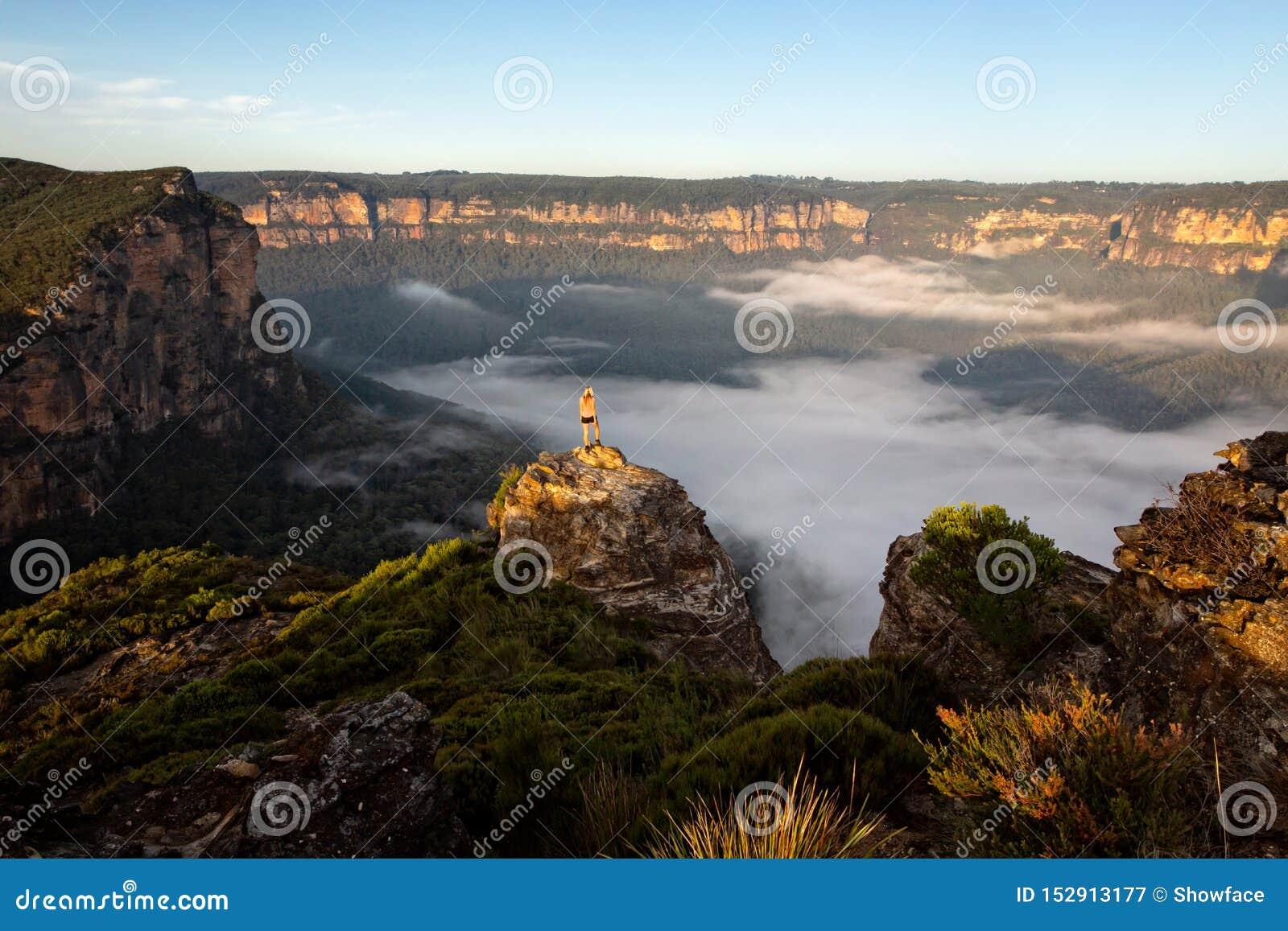 Οδοιπόρος που παίρνει κατά τις θαυμάσιες απόψεις των βουνών και των κοιλάδων ως θόριο