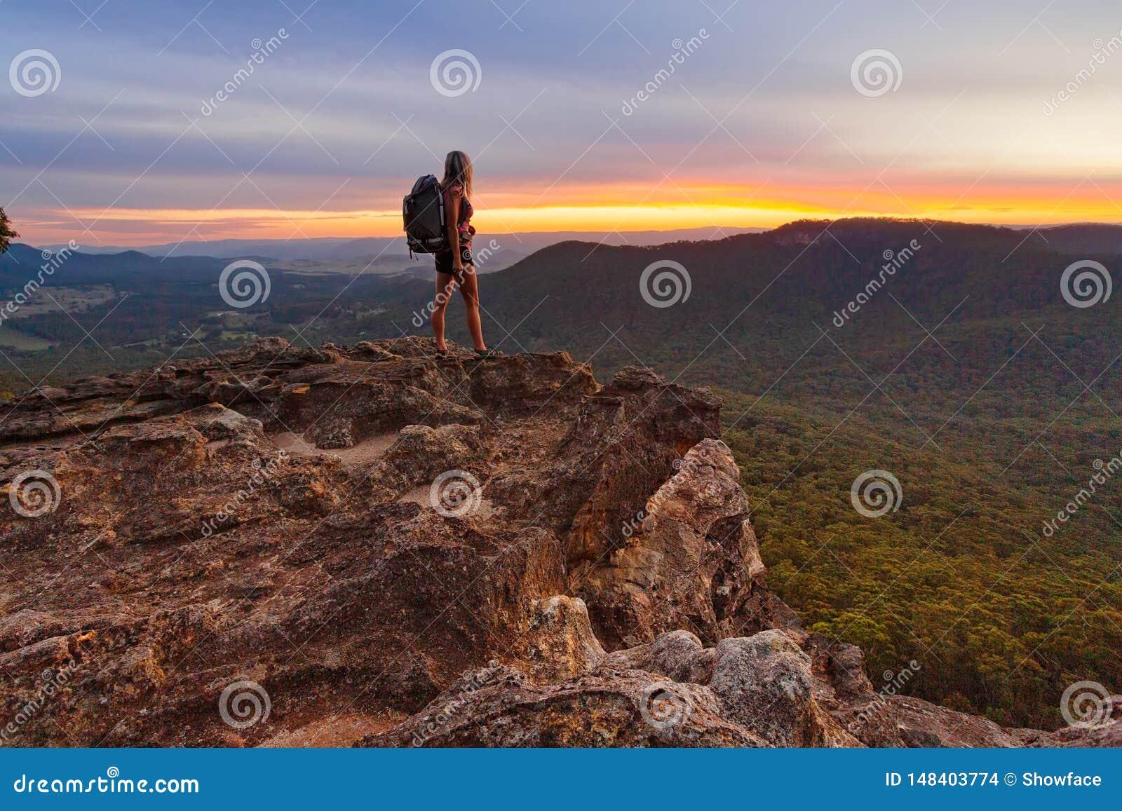 Οδοιπόρος που προσέχει το τελευταίο φως στα βουνά