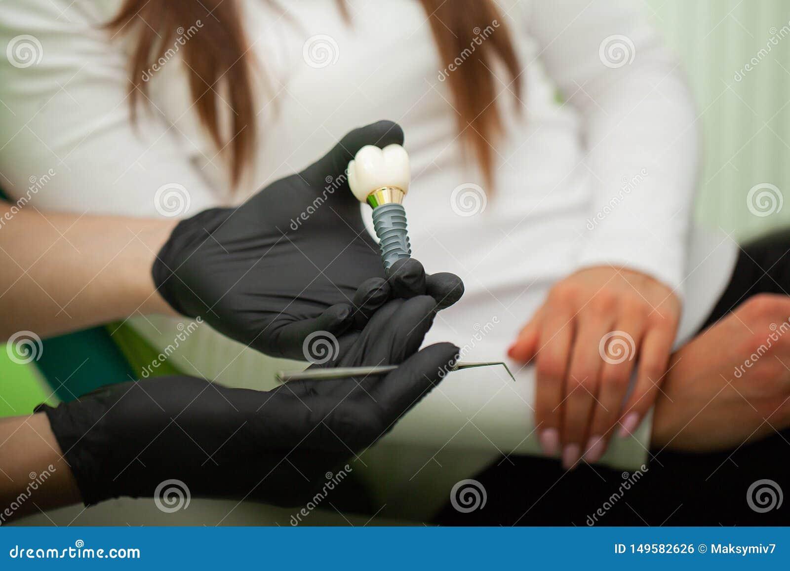 Οδοντίατρος που εξηγεί το πρότυπο δοντιών στο θηλυκό ασθενή Τεχνικοί πυροβολισμοί σε ένα οδοντικό prothetic εργαστήριο