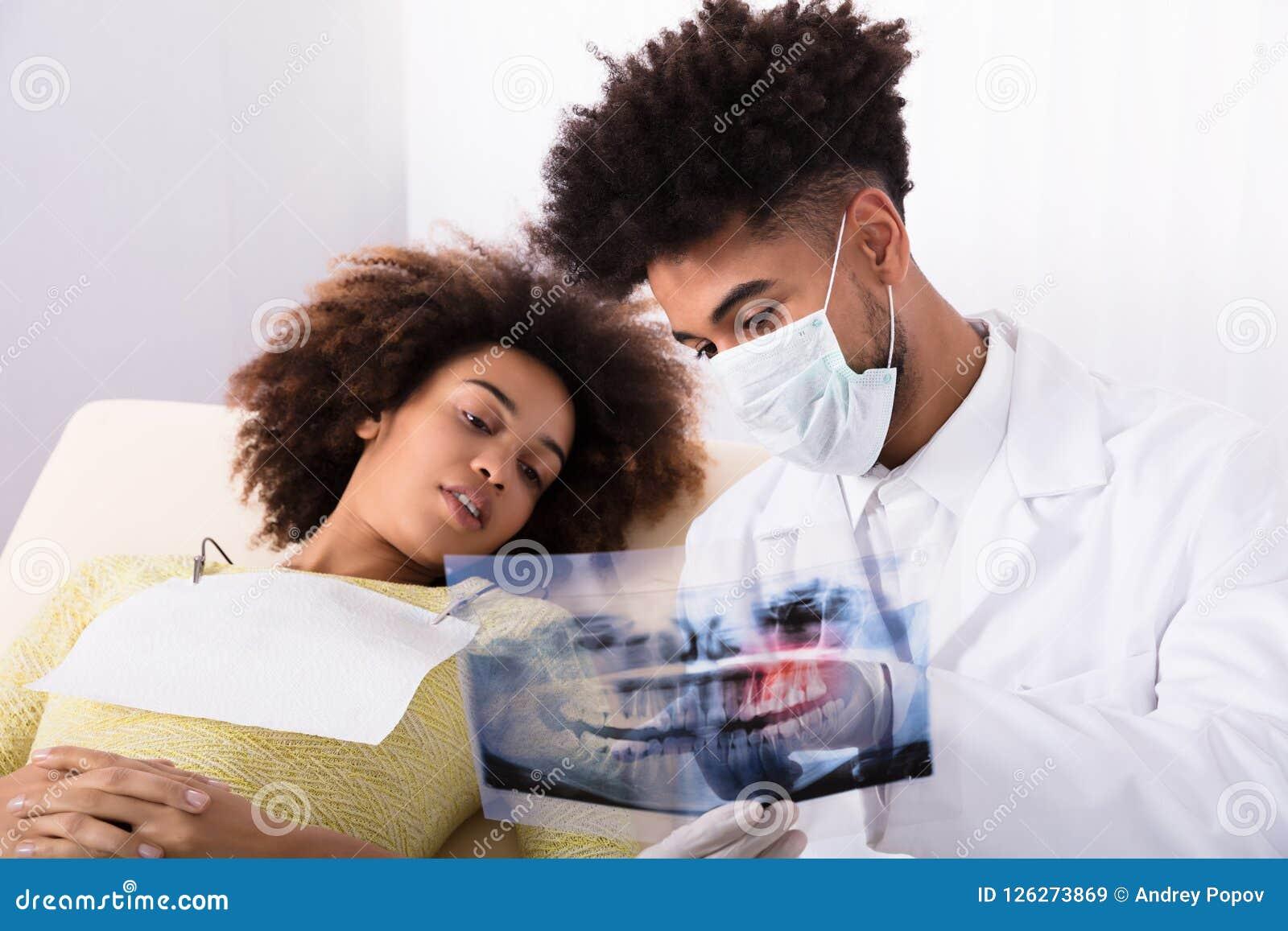 Οδοντίατρος που παρουσιάζει ακτίνα X δοντιών στο θηλυκό ασθενή