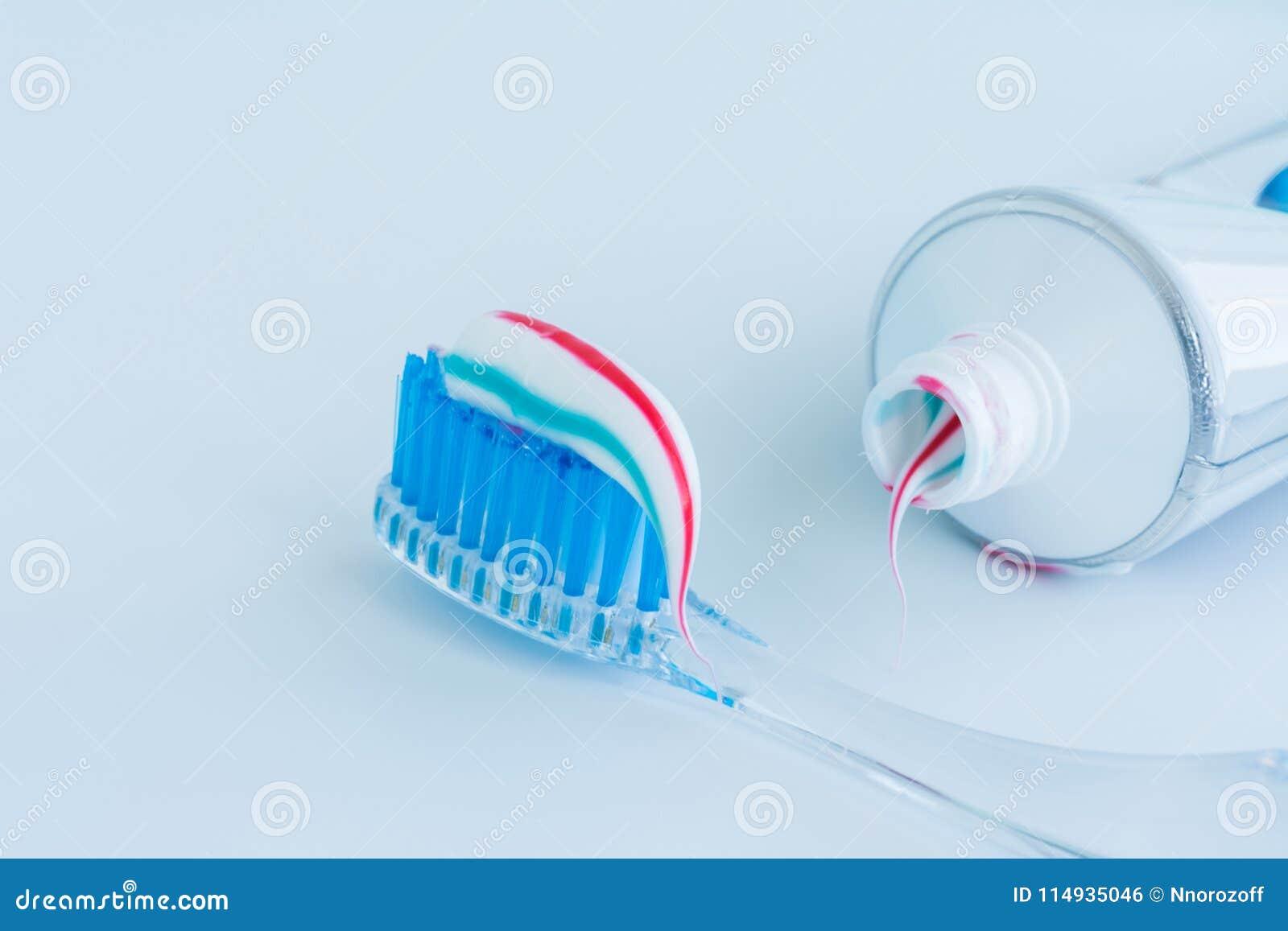 Οδοντόβουρτσα του σαφούς πλαστικού με τις μπλε σκληρές τρίχες, άσπρες μπλε κόκκινες συμπιέσεις οδοντόπαστας από έναν σωλήνα