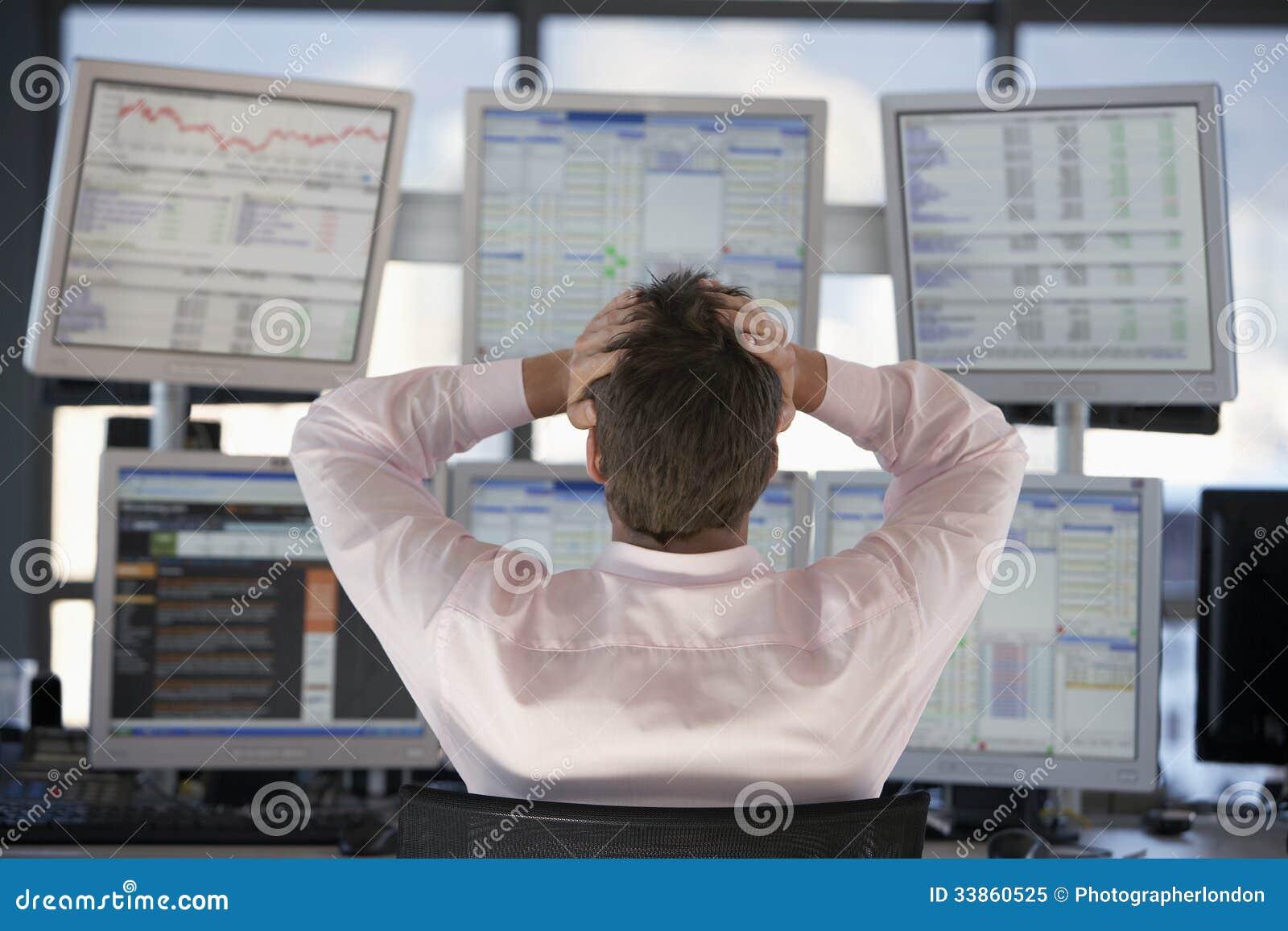 Οθόνες υπολογιστή προσοχής εμπόρων αποθεμάτων με τα χέρια στο κεφάλι
