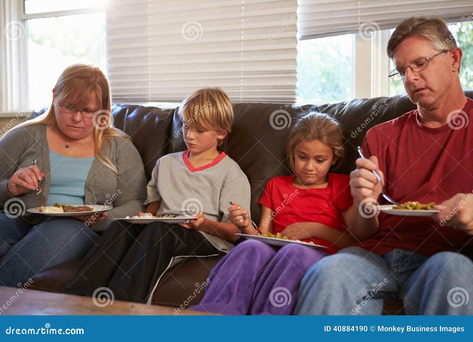 Οικογένεια με τη φτωχή συνεδρίαση διατροφής στον καναπέ που τρώει το γεύμα