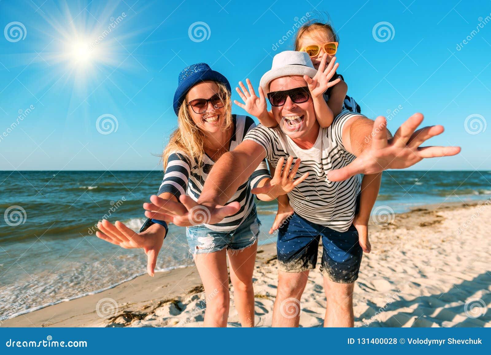 οικογένεια παραλιών ευ&ta Άνθρωποι που έχουν τη διασκέδαση στις θερινές διακοπές Πατέρας, μητέρα και παιδί στην μπλε θάλασσα και