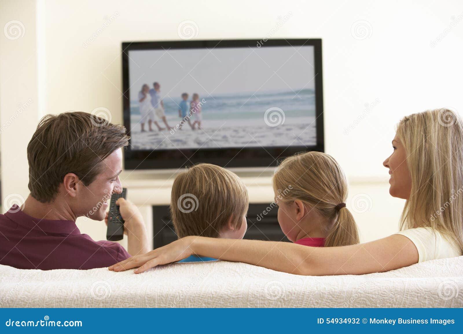 Οικογένεια που προσέχει την της μεγάλης οθόνης TV στο σπίτι