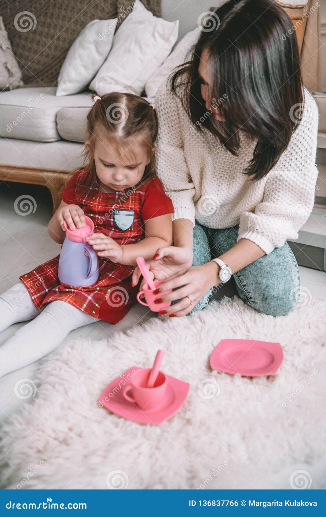 οικογενειακή ευτυχής & Η μητέρα και το κορίτσι κορών της παίζουν το τσάι-κόμμα και πίνουν το τσάι από τα φλυτζάνια στο δωμάτιο πα