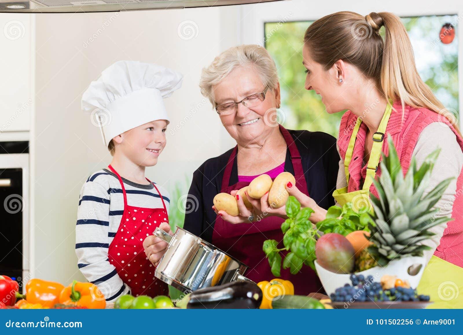 Οικογενειακό μαγείρεμα στην οικογένεια multigenerational με το γιο, μητέρα,