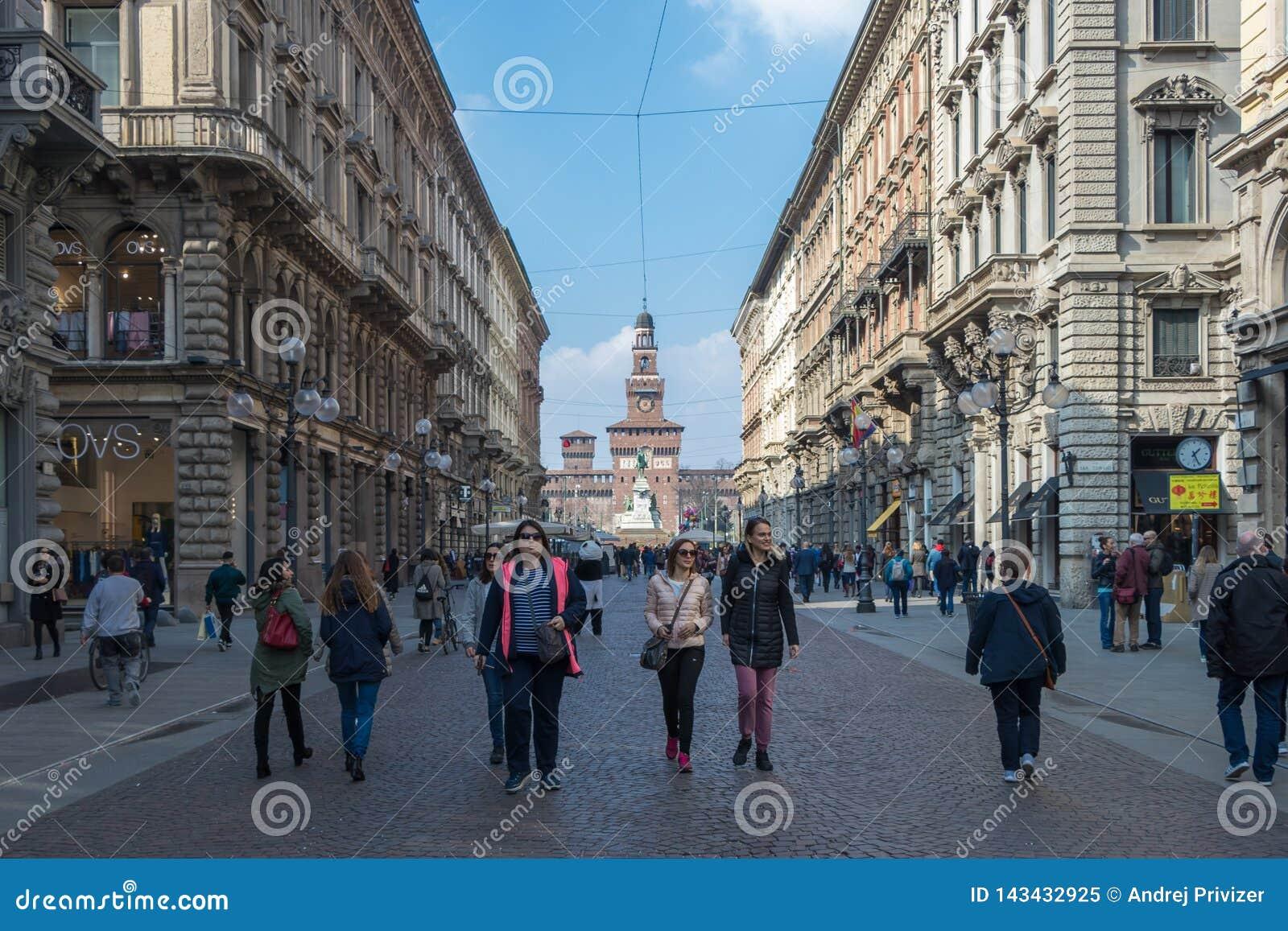 Οι άνθρωποι περπατούν στην οδό μέσω του Dante στο υπόβαθρο το Sforzesco Castle, Ιταλία