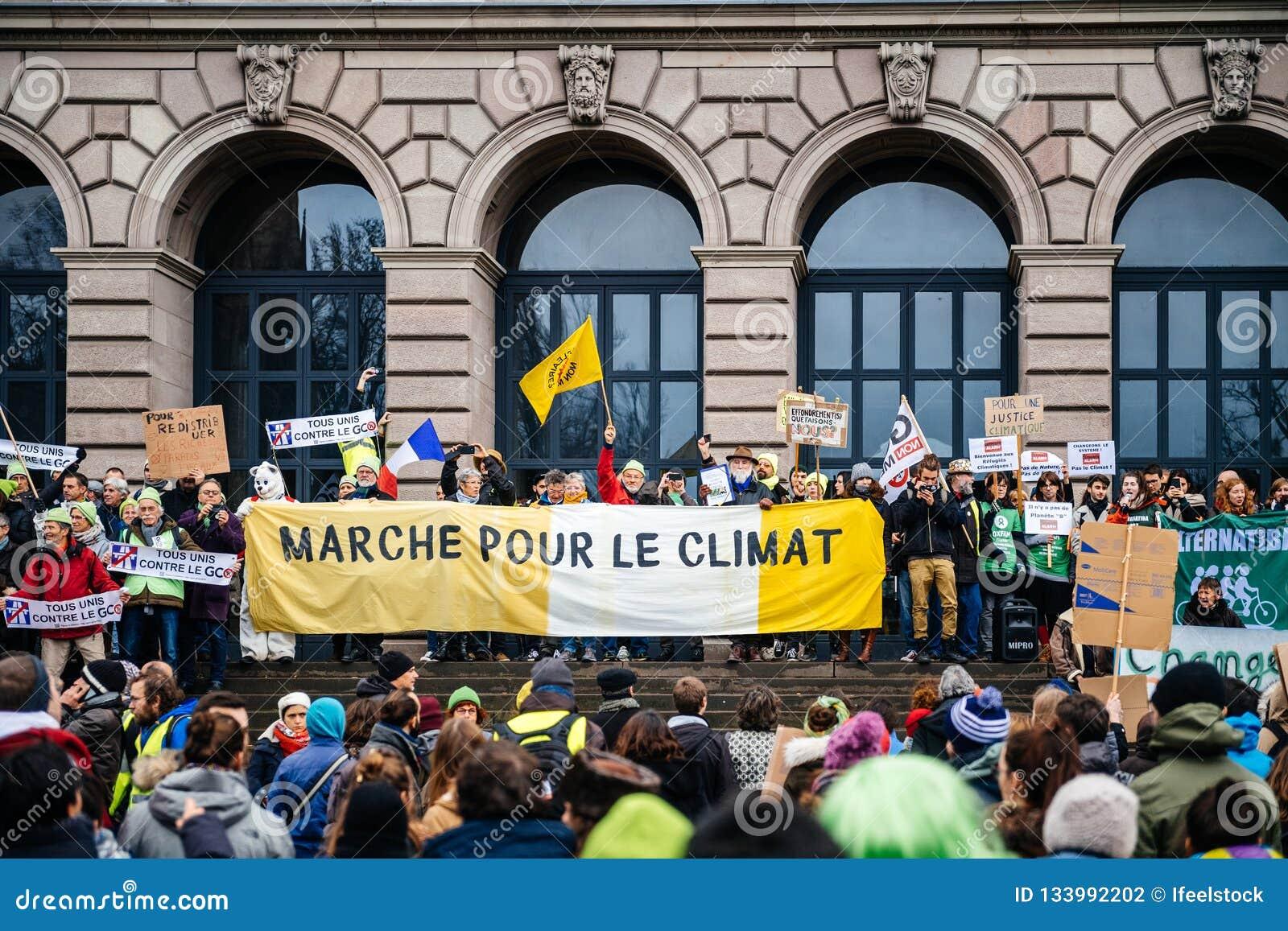 Οι άνθρωποι που βαδίζουν στο Marche χύνουν LE Climat στη Γαλλία μπροστά από το U