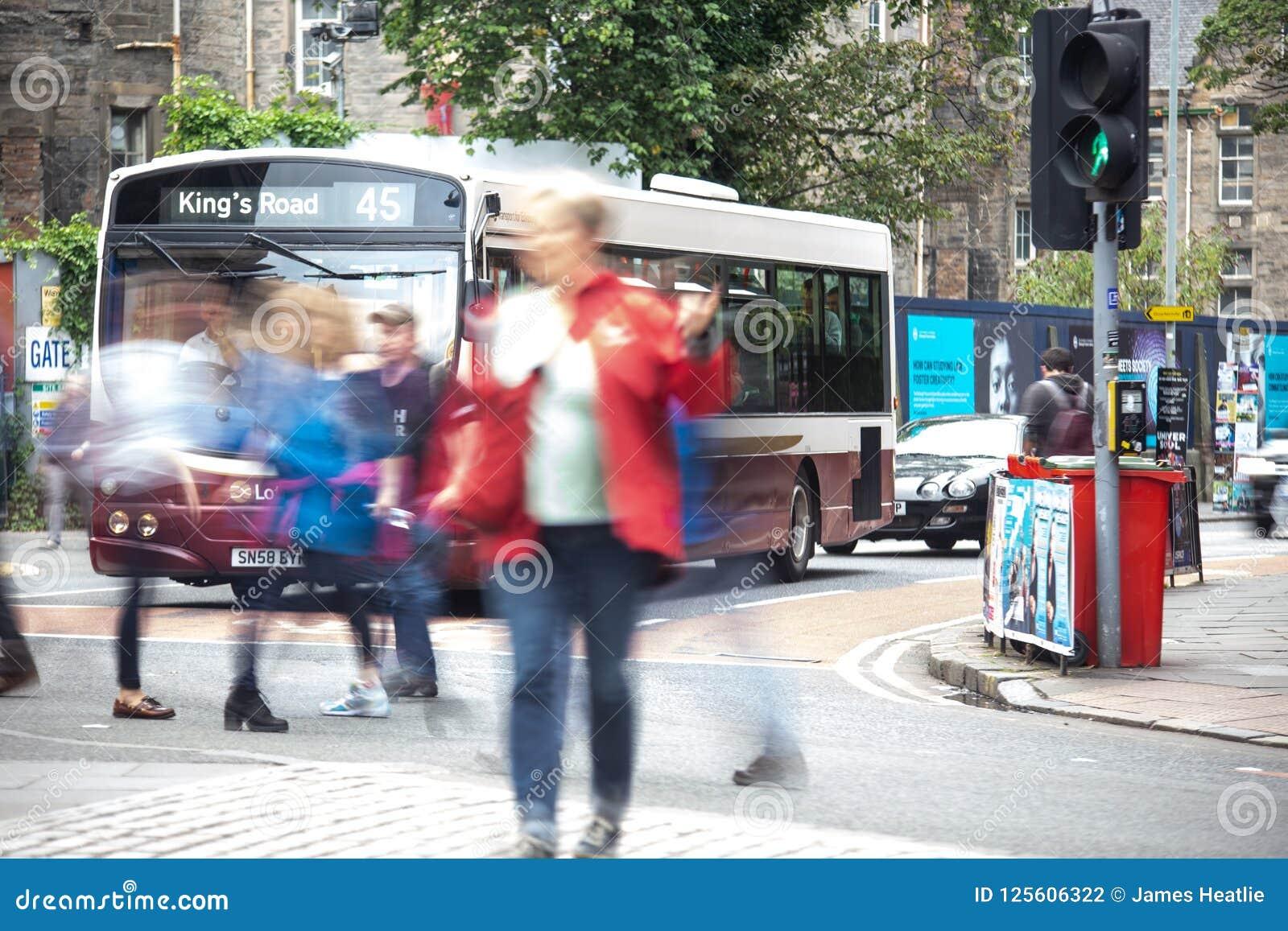 Οι άνθρωποι που διασχίζουν τη διάβαση πεζών στο Εδιμβούργο ως οδικό λεωφορείο βασιλιάδων περιμένουν στα φω τα