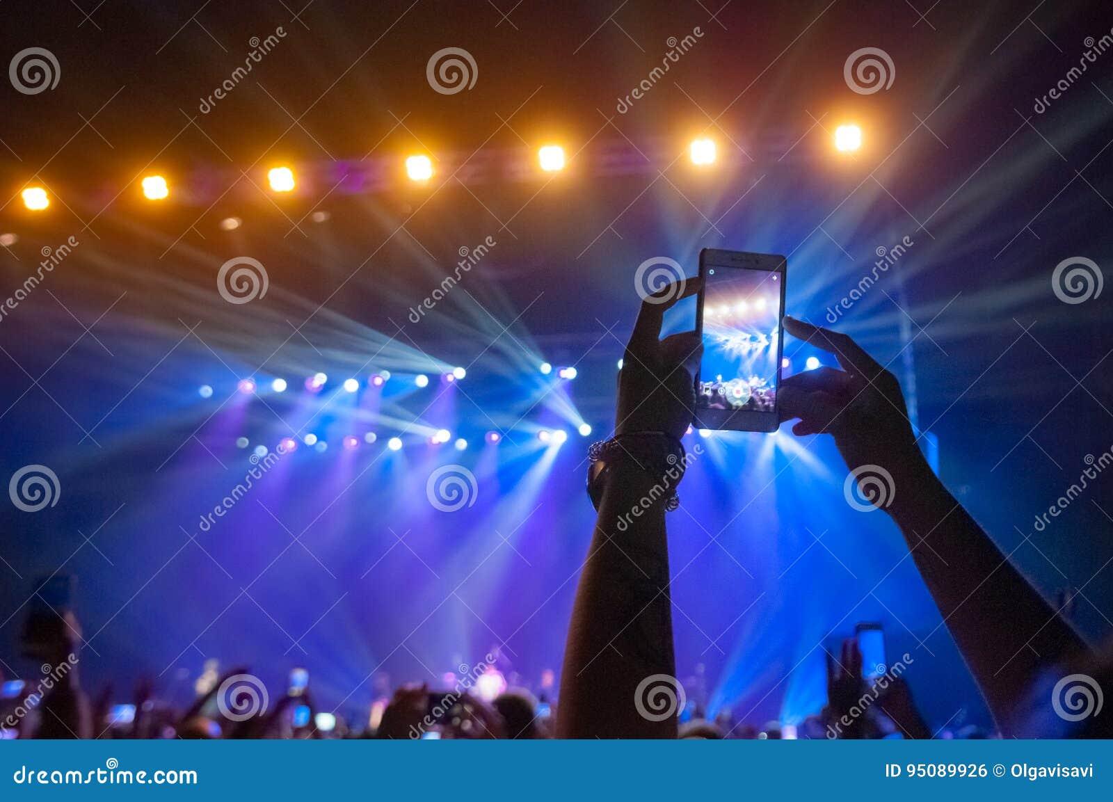Οι άνθρωποι στο πλήθος σε μια συναυλία κάνουν τις τηλεοπτικές καταγραφές και pics