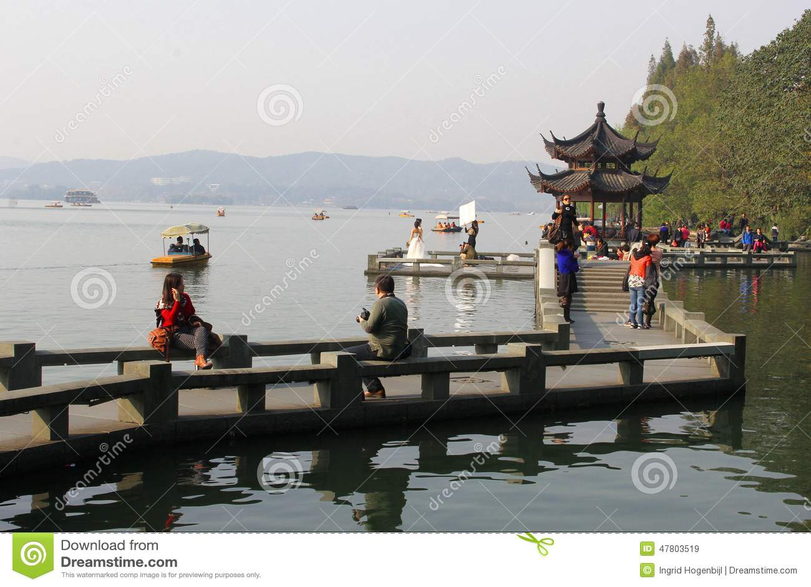 Οι άνθρωποι χαλαρώνουν κατά μήκος της δυτικής λίμνης της ΟΥΝΕΣΚΟ σε Hangzhou, Κίνα