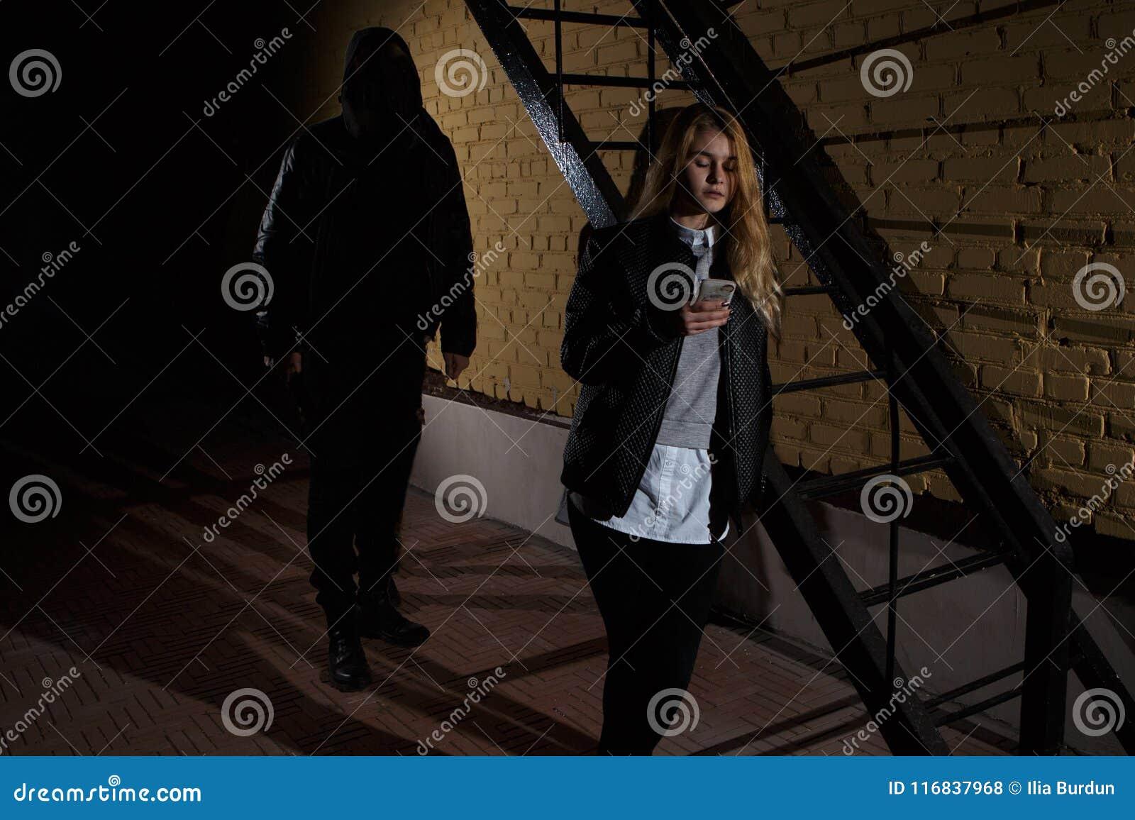 Οι έννοιες ληστείας εννοιών εγκλήματος ένας ληστής στόχευσαν το αιχμηρό μαχαίρι του σε μια γυναίκα για να ληστεψουν τα πολύτιμα π