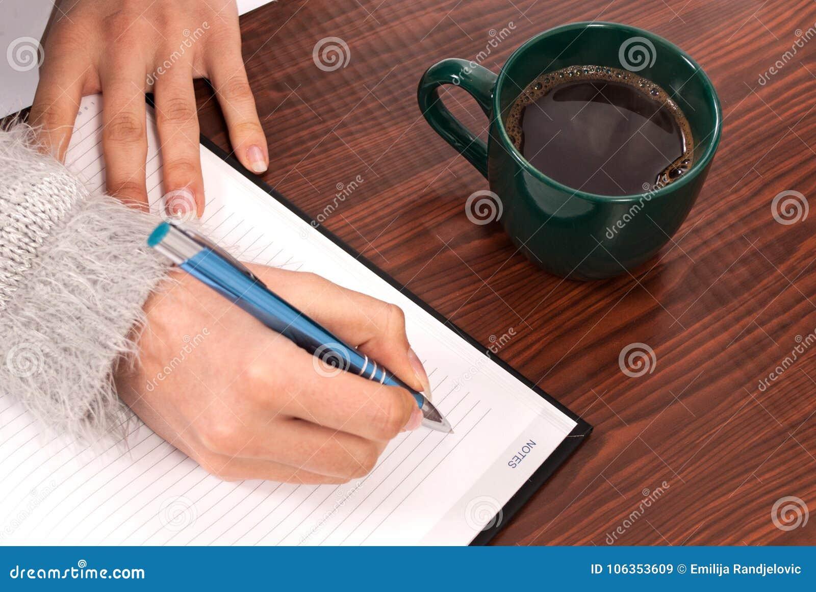Οι γυναίκες που γράφουν στο σημειωματάριο στο ξύλινο γραφείο και πίνουν τον καφέ