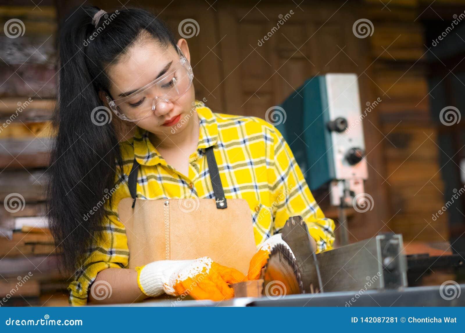 Οι γυναίκες που στέκονται είναι τέχνη που λειτουργεί το κομμένο ξύλο σε έναν πάγκο εργασίας με τα κυκλικά εργαλεία δύναμης πριονι