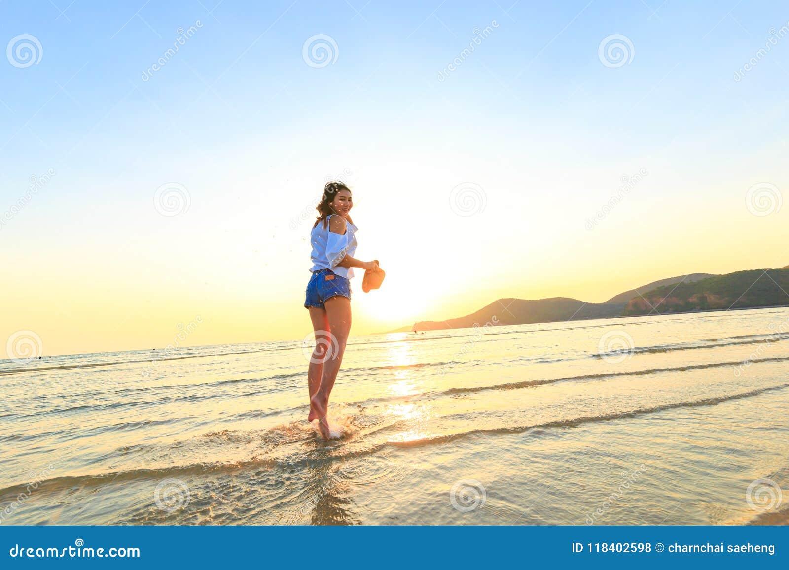 Οι γυναίκες στέκονται και κρατούν το καπέλο στην παραλία μεταξύ του ηλιοβασιλέματος