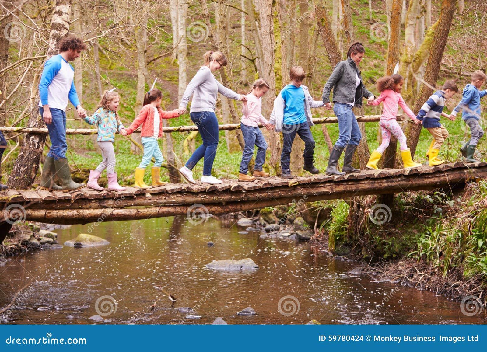 Οι ενήλικοι με τα παιδιά στη γέφυρα στην υπαίθρια δραστηριότητα στρέφονται