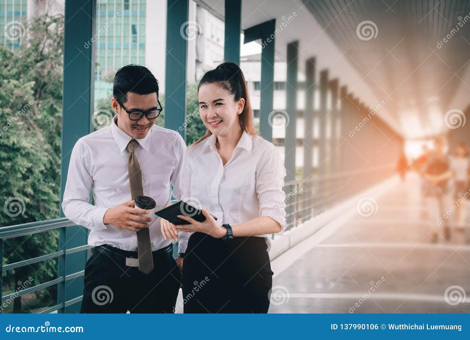 Οι επιχειρηματίες που εργάζονται στο ψηφιακό διάγραμμα ταμπλετών και ανάλυσης υποβάλλουν έκθεση μαζί στη διάβαση πεζών στο κτήριο