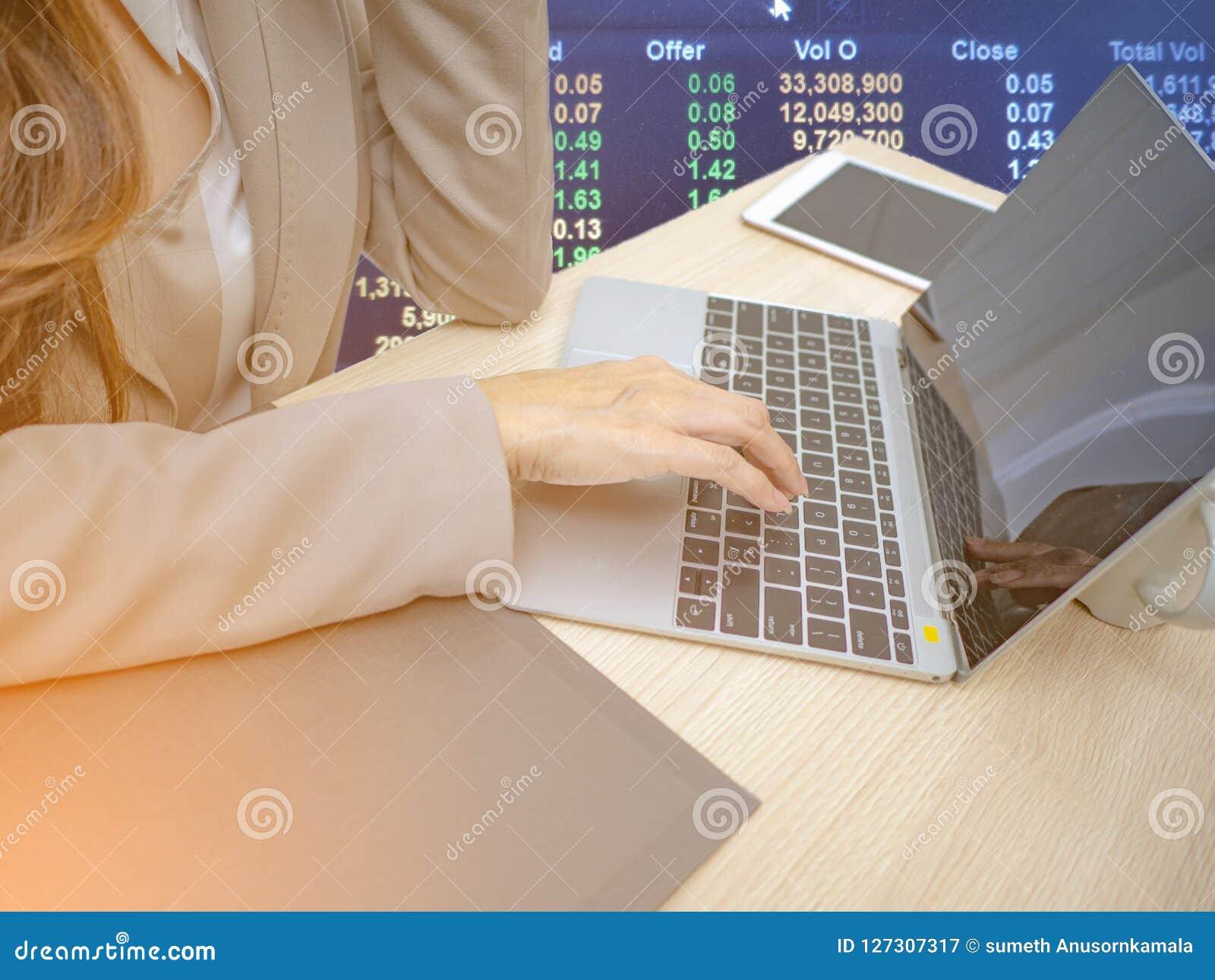 Οι επιχειρησιακές γυναίκες δίνουν το lap-top χρήσης για το εμπόριο στο χρηματιστήριο